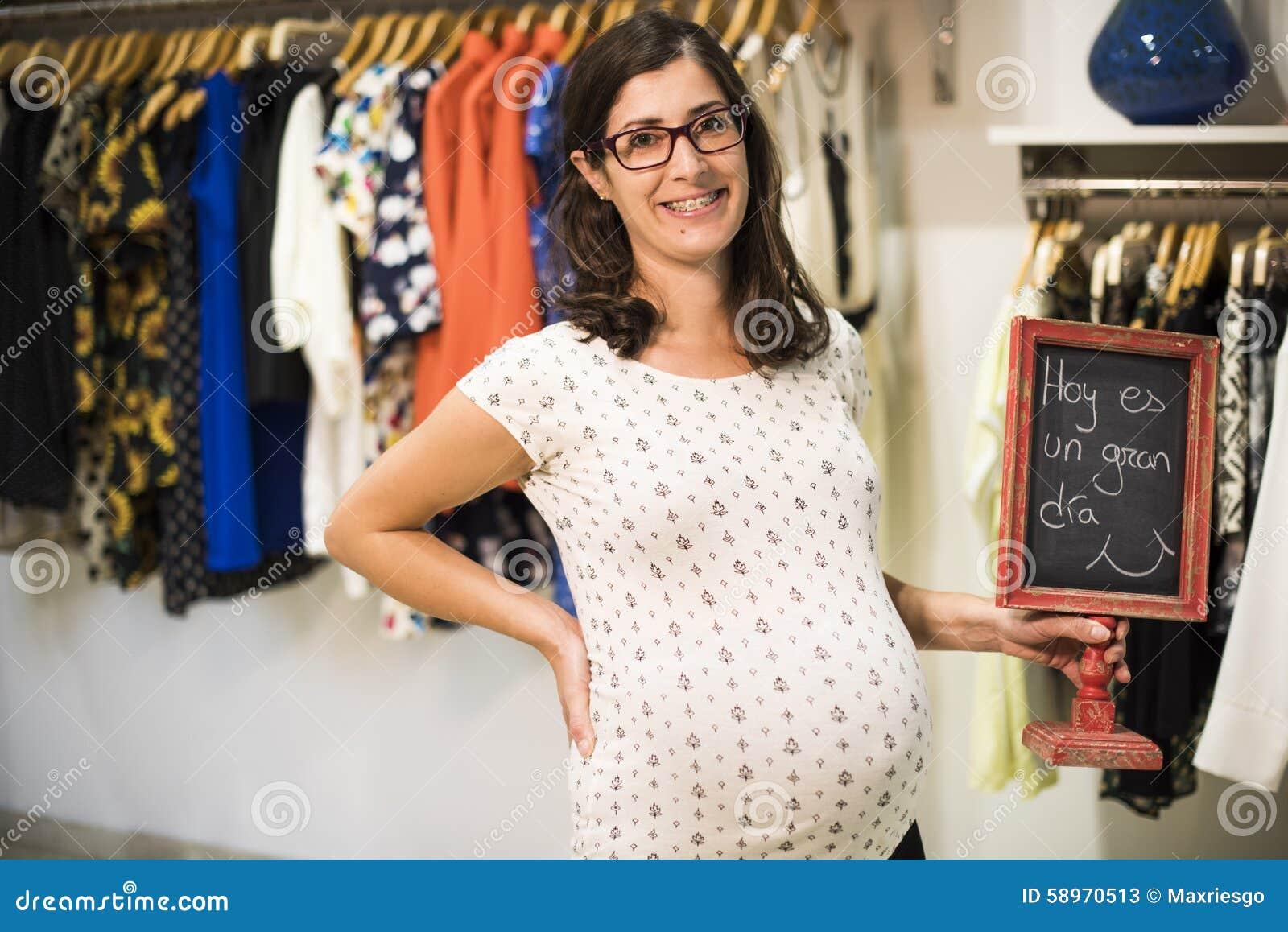 444fd00c8be3b4 Zwangere Vrouw Die In Klerenopslag Sommige Kleren Kijken Stock ...