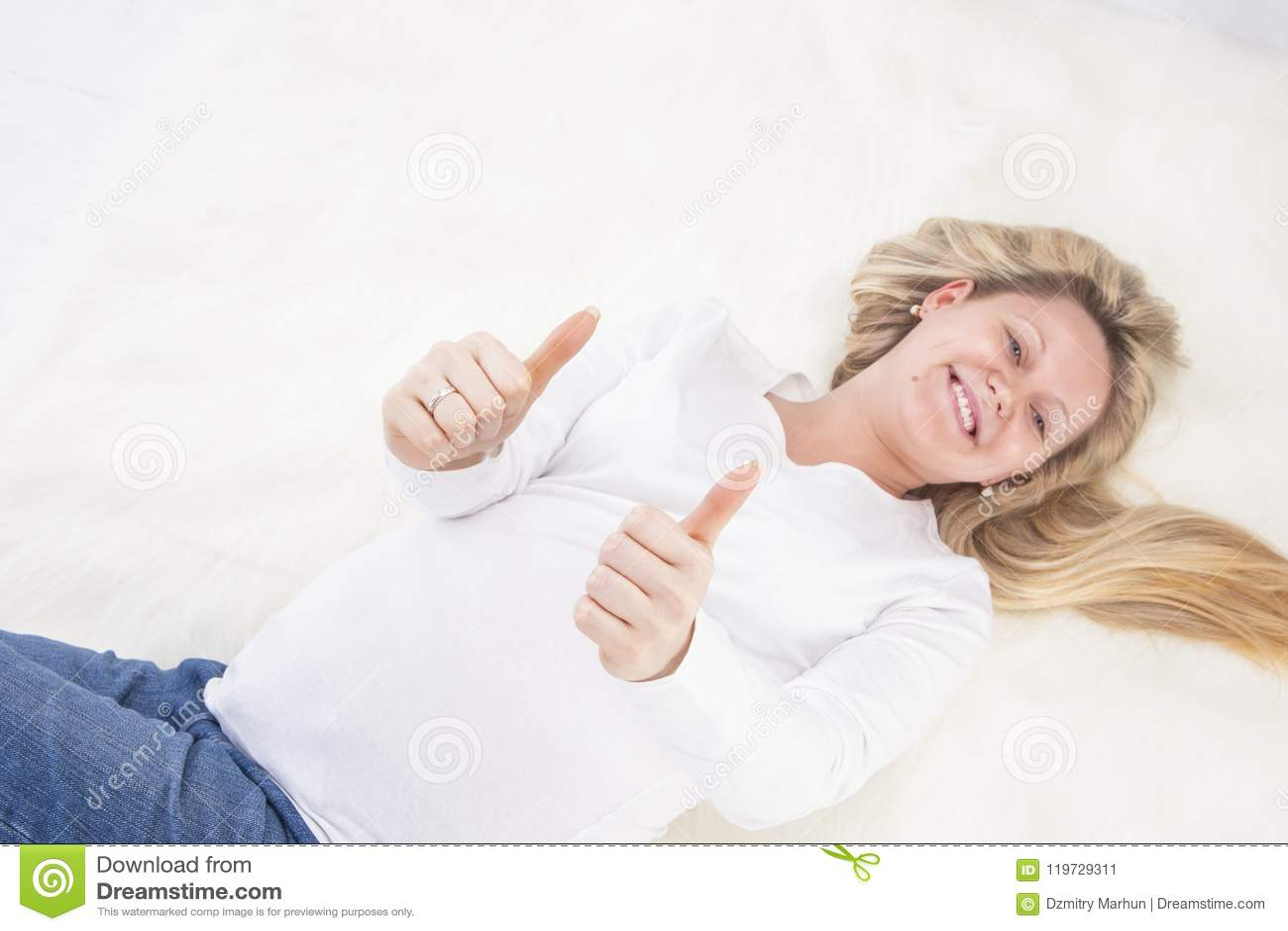 Zwangere Vrouw die op Bonttapijt leggen in Witte Overhemd en Jeans