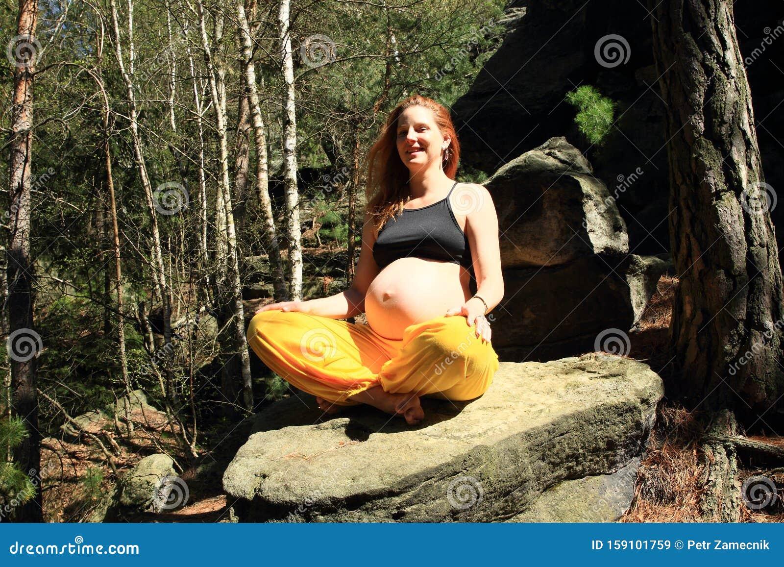 Zwangere Vrouw Die Op Steen Zit In Een Eenvoudige Yoga ...