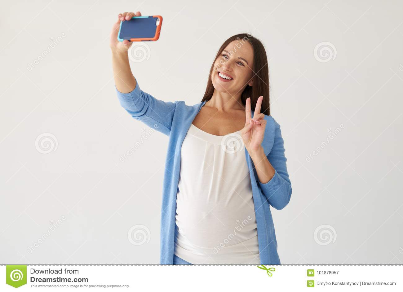 Zwangere vrouw die selfie tegen witte achtergrond maken