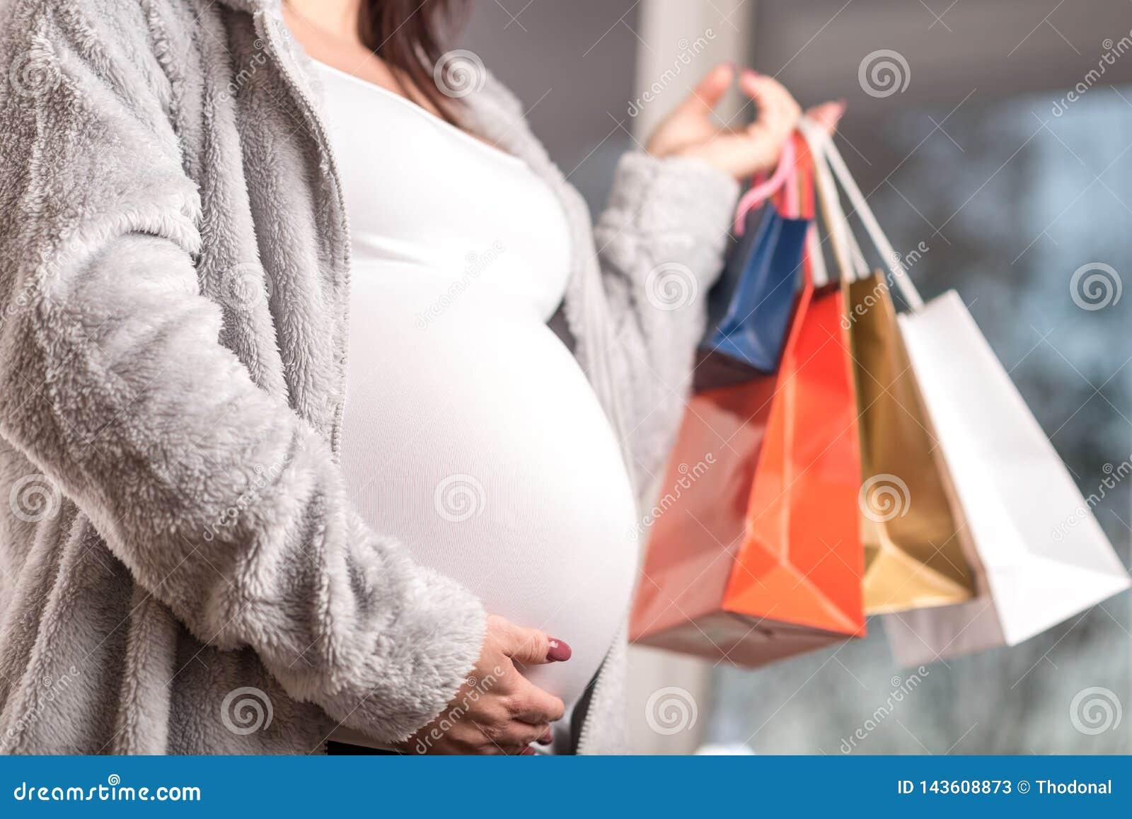 Zwangere vrouw met het winkelen zakken wat betreft haar buik