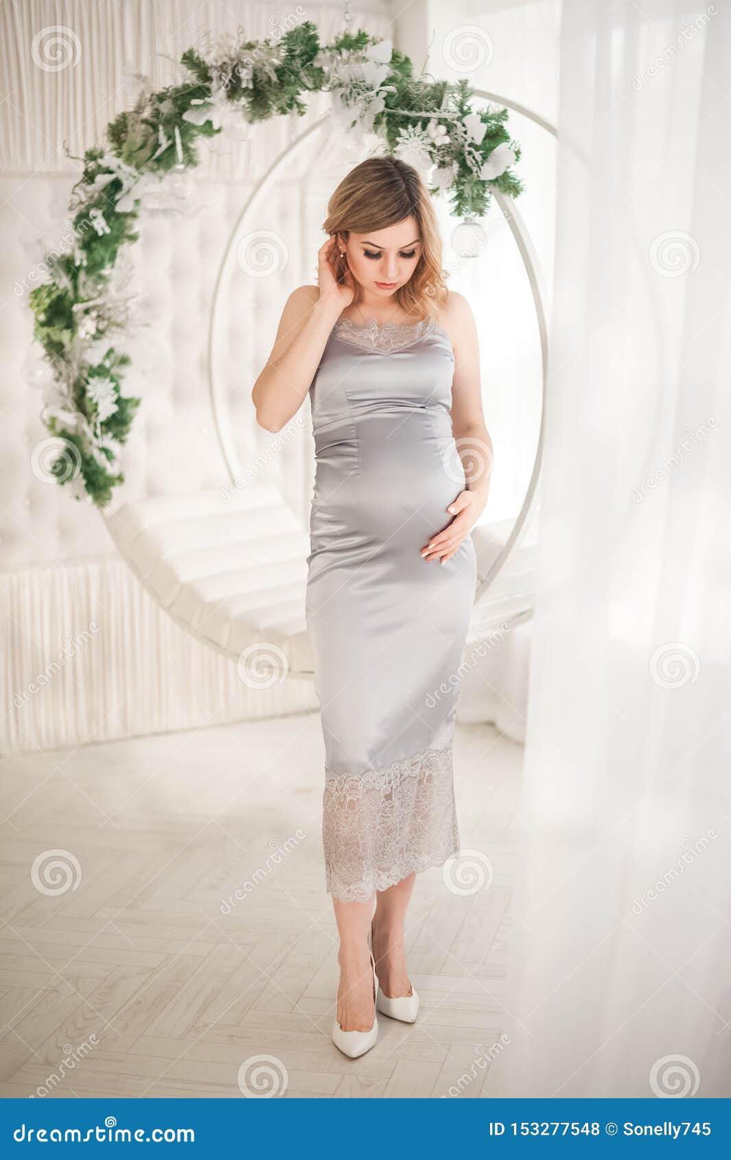 Zwangere vrouw in peignoir met schommeling dat voor het Nieuwjaarclose-up verfraaid is Een vrouw die op een baby in een zilveren