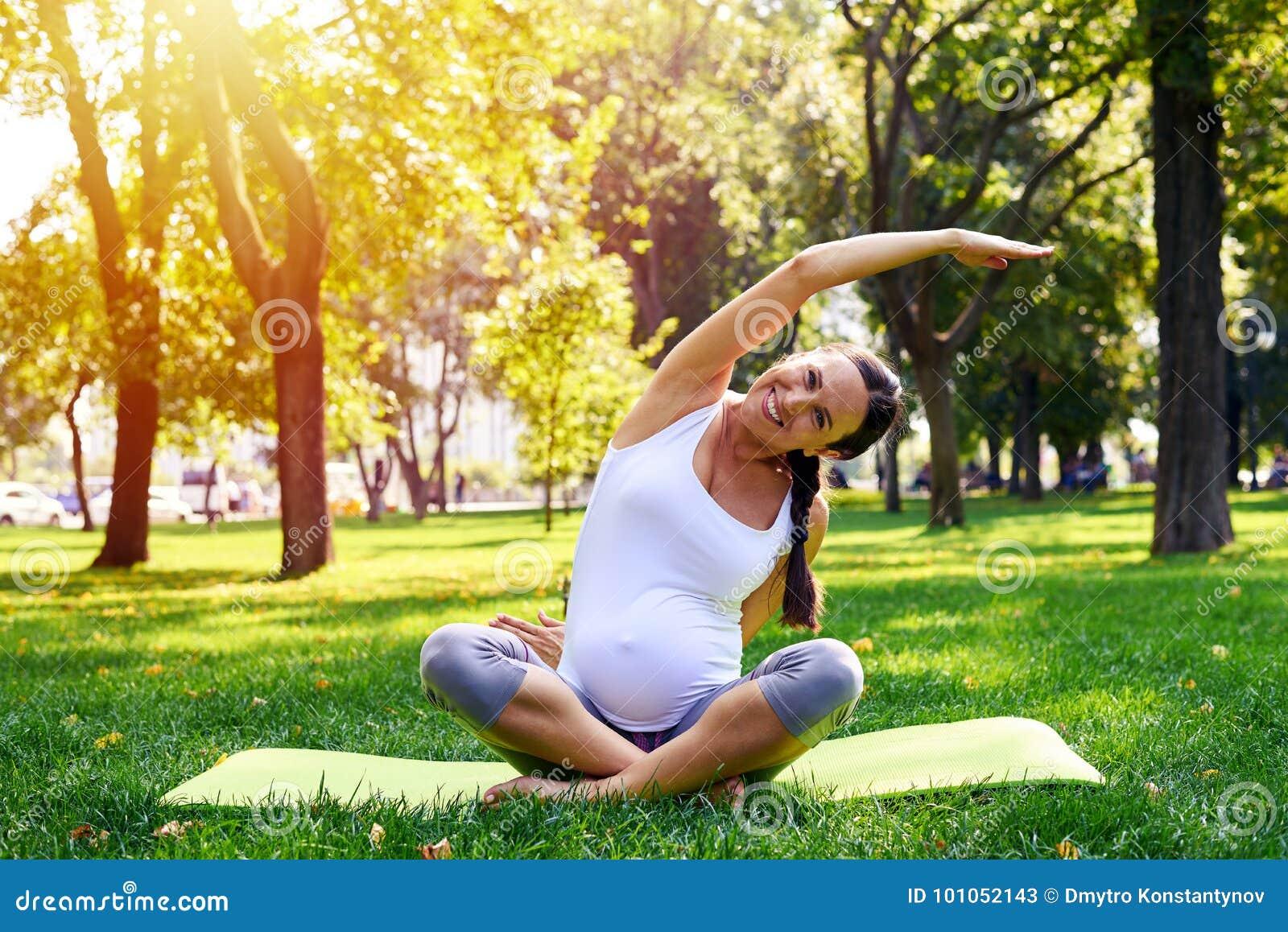 Zwangere vrouw in zich het goede vorm uitrekken op yogamat in openlucht