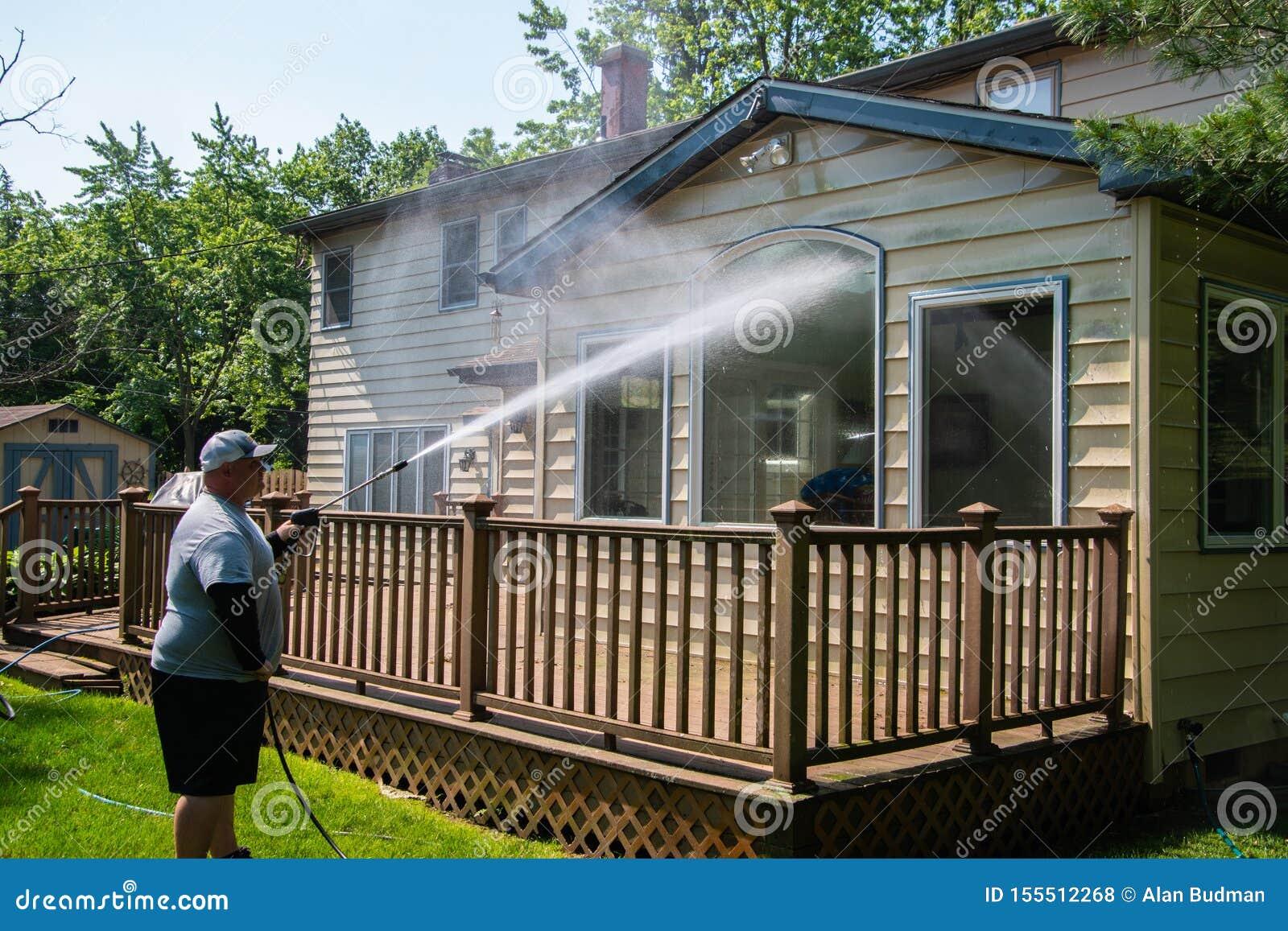 Zware echtgenootmacht die grote vensters op de rug van een huis over een bruin houten dek met een drukwasmachine wassen