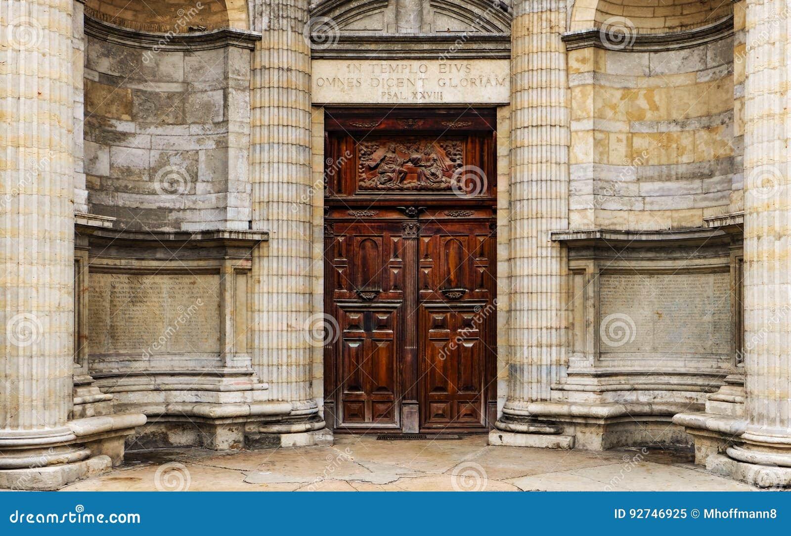 Zware houten dubbele deur buiten een oude kerk met godsdienstige hulp en inschrijvingen