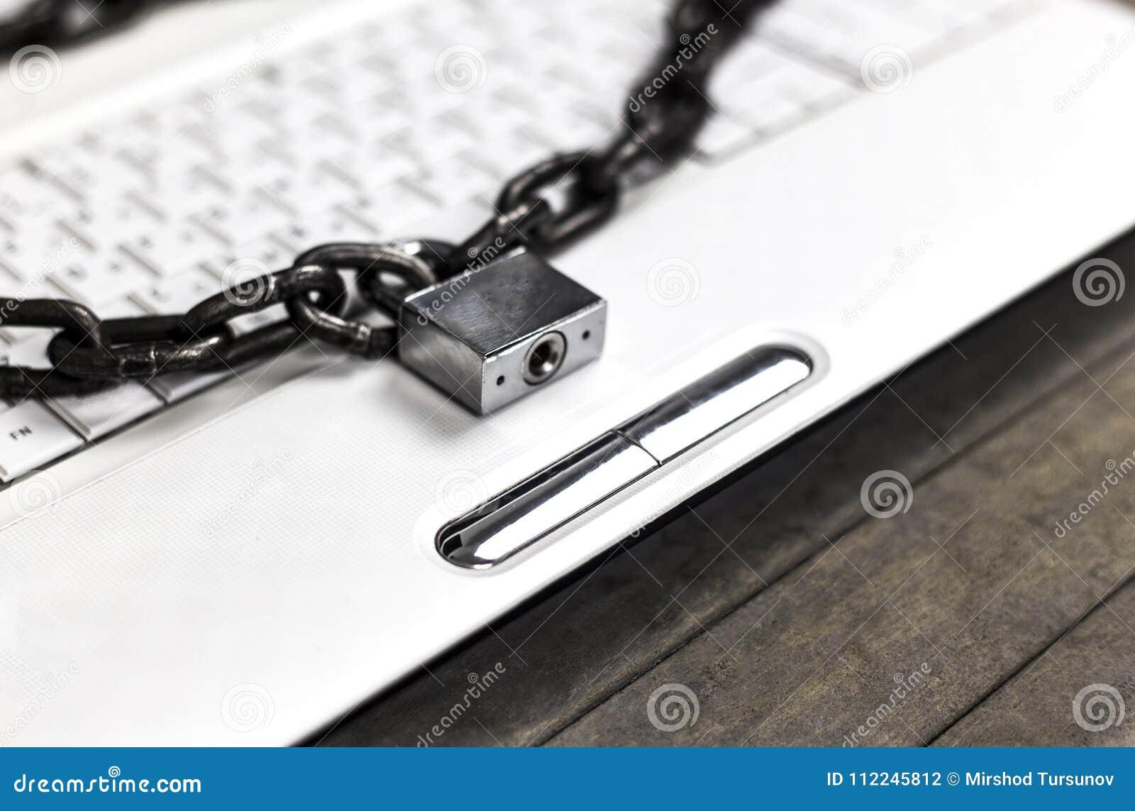 Zware ketting met een hangslot rond laptop op grijze lijst