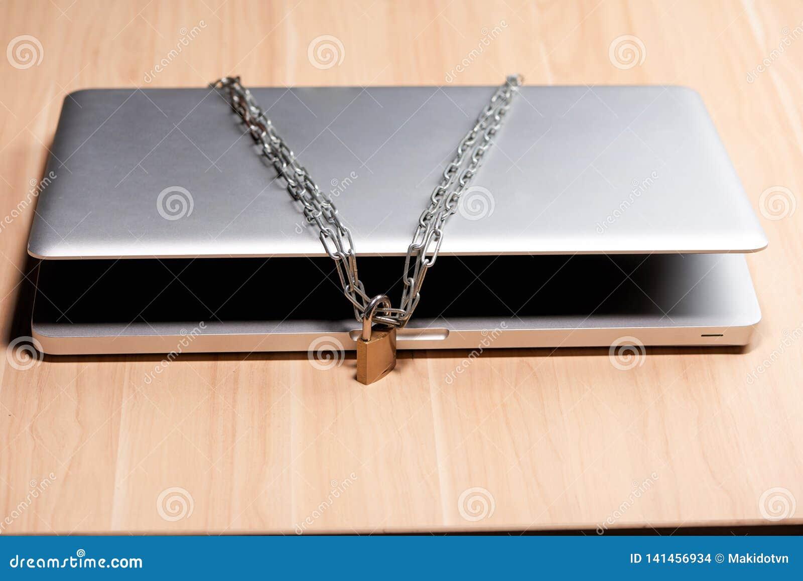 Zware ketting met een hangslot rond laptop op lijst