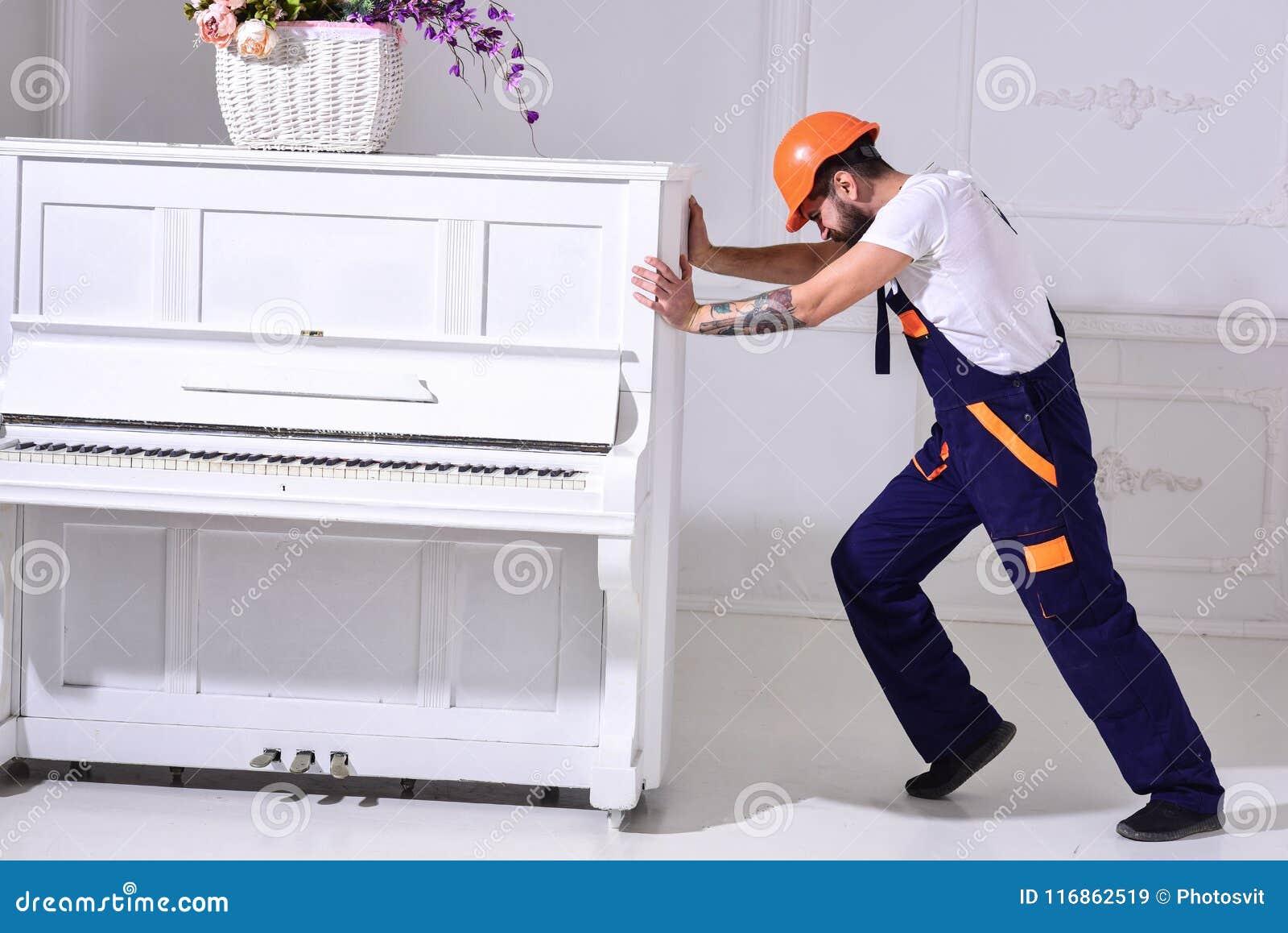 Zware ladingenconcept De lader beweegt pianoinstrument De koerier levert meubilair, beweging uit, verhuizing Mens met baard