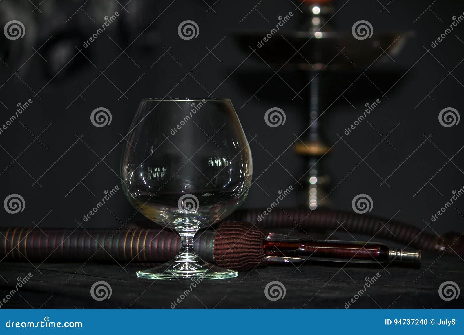 Zware waterpijprook in een cognacglas op een grijze achtergrond, waterpijpbuis