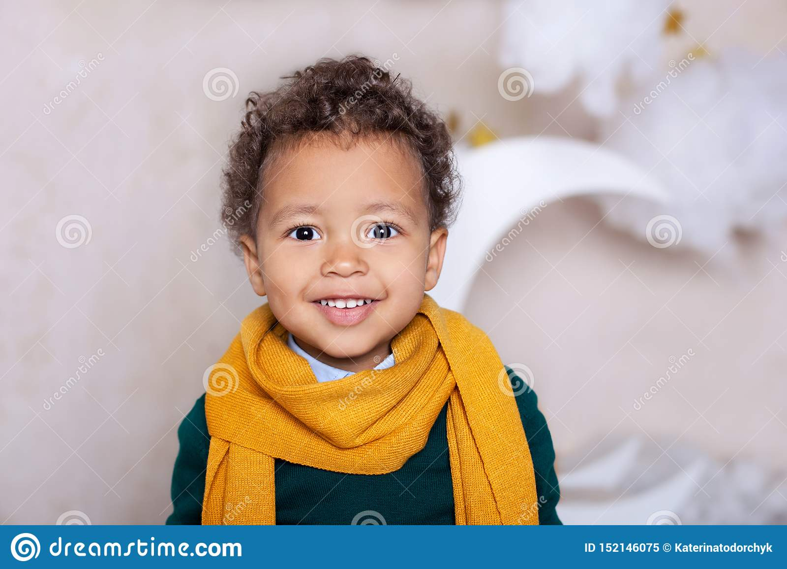 Zwart jongens dicht omhooggaand Portret Portret van een vrolijke glimlachende jongen in een gele sjaal de baby glimlacht Weinig A