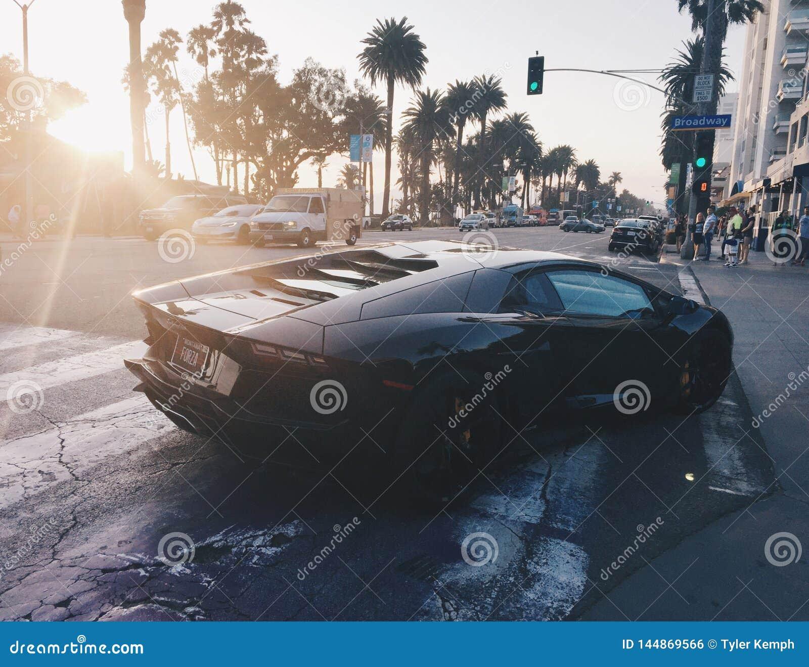 Zwart Lamborghini bij zonsondergang in Santa Monica California