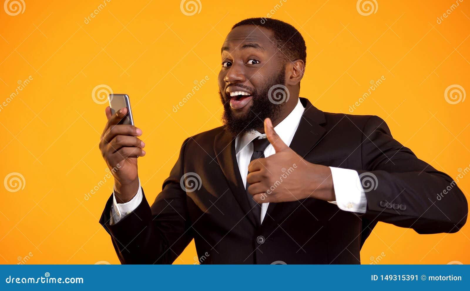 Zwart mannetje die duim-op tevreden met mobiele toepassingsprestaties tonen, hulpmiddel