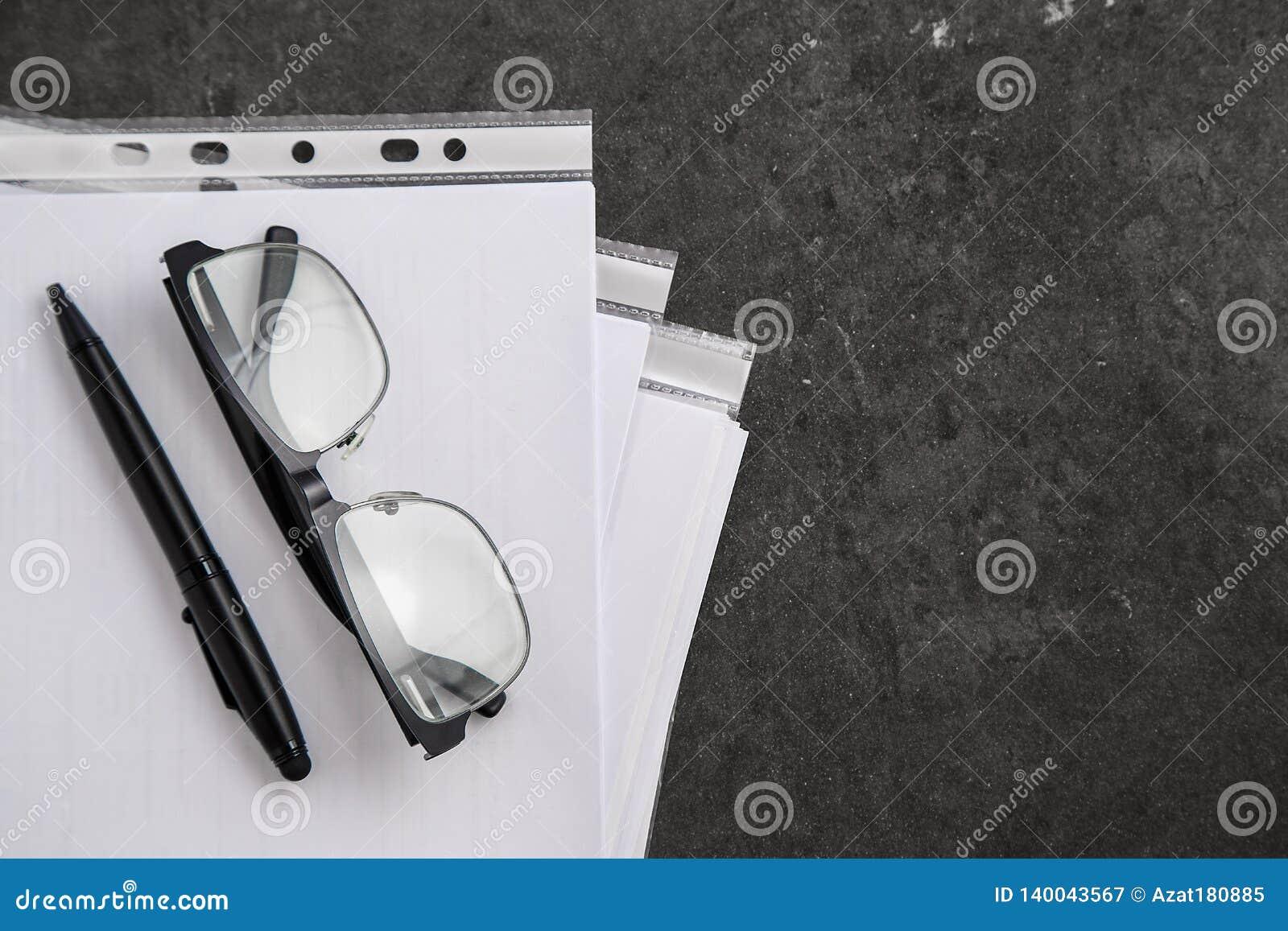 Zwart-omrande optische glazen op documenten op grijze marmeren achtergrond