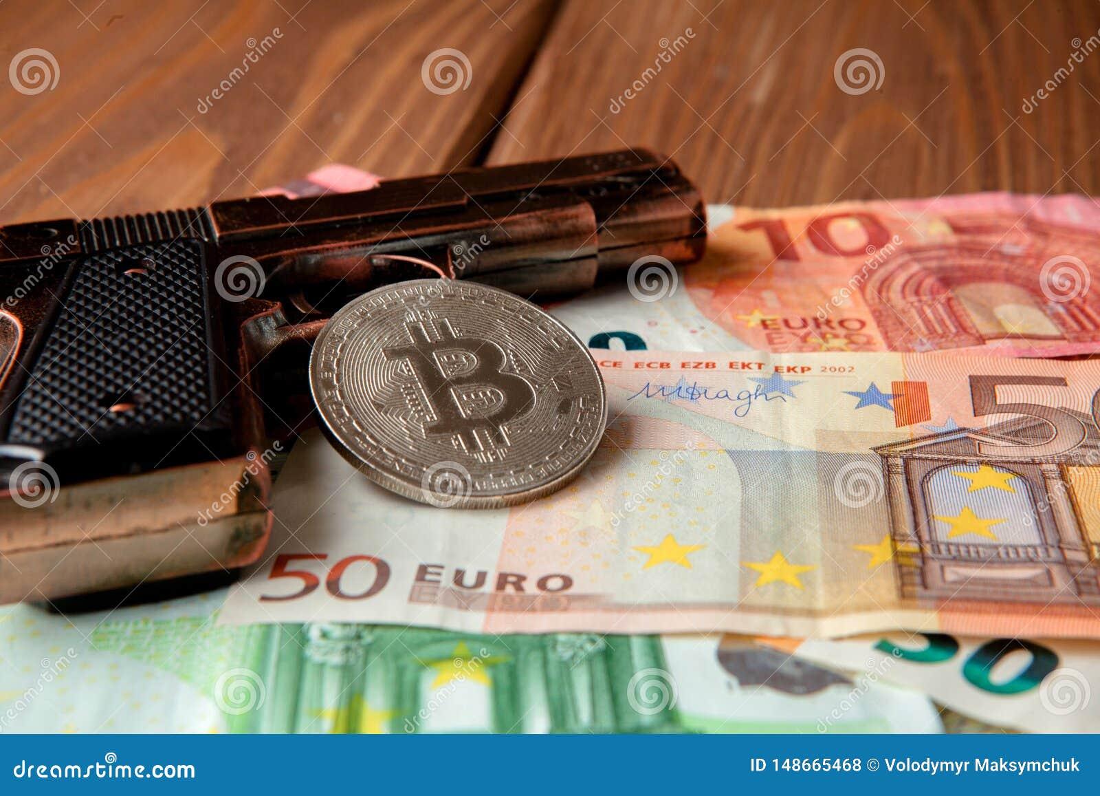 Zwart pistool, euro en muntstuk in de vorm van bitcoin op houten achtergrond