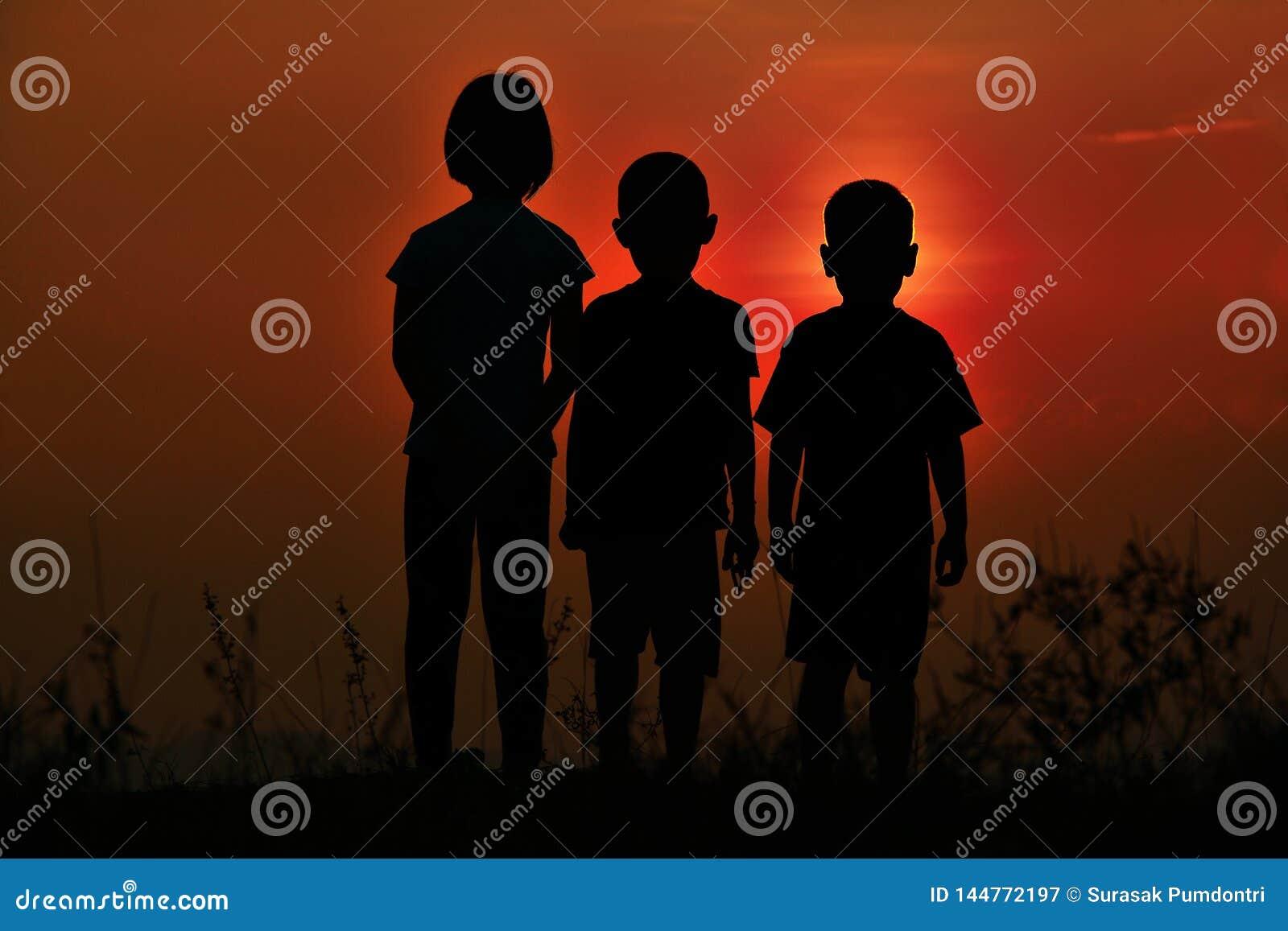 Zwart silhouet van drie kinderen die zich verenigen Er is een hemel bij zonsondergang