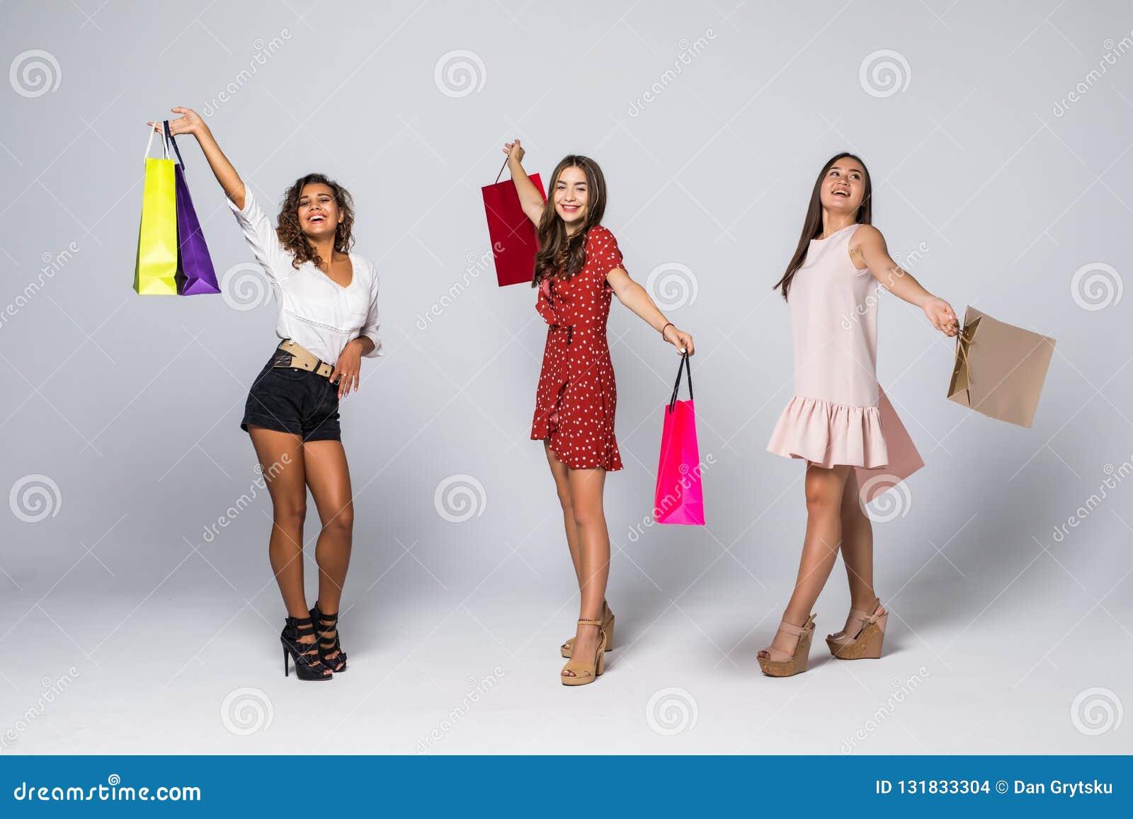 Zwart vrijdagconcept Het portret van vrolijke drie mengde rasvrouwen die kleurrijke zakken in opgeheven handen houden genietend v