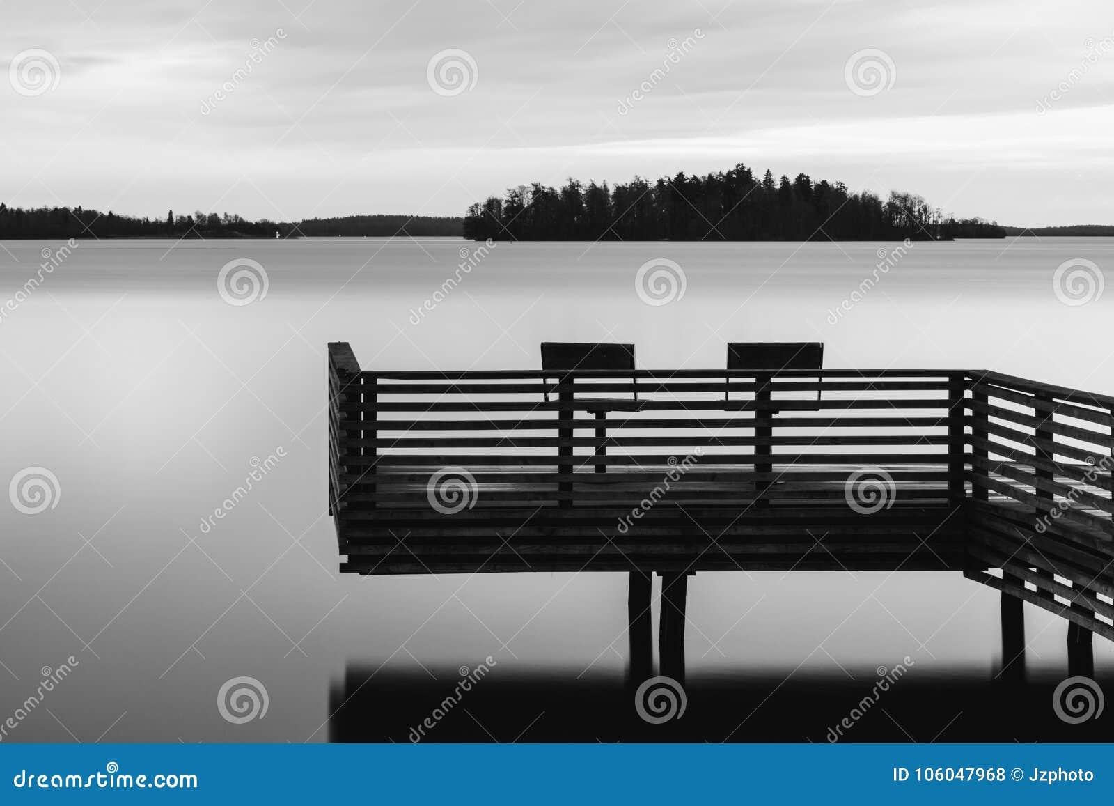 Zwart-wit rustig landschap van een meer met pijler en twee stoelen