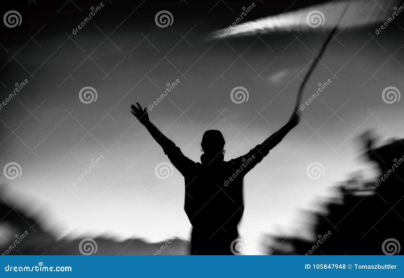 Zwart-wit silhouet van een jonge vrouw met opgeheven wapens
