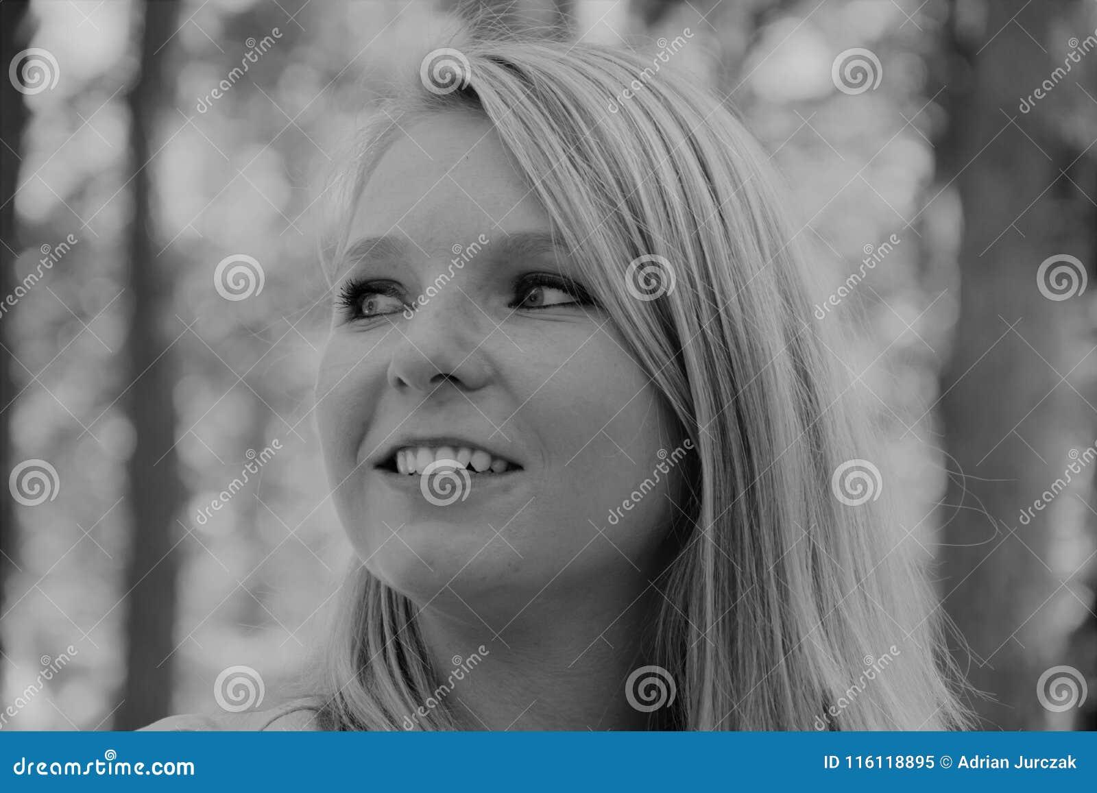 Zwart-witte foto van het profiel van een het glimlachen vrouwen` s gezicht