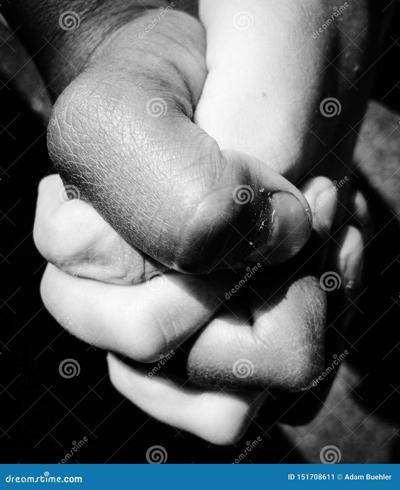Zwart-witte foto van zwarte jong geitjehand en witte jong geitjehand