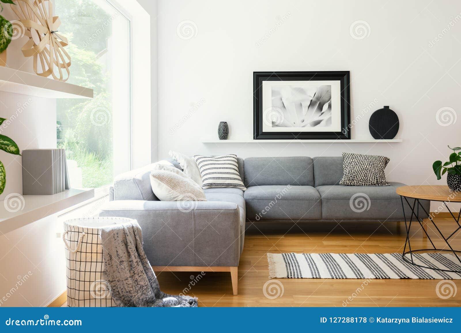 Zwart-witte textiel en decoratie in een klassiek Skandinavisch binnenland van de stijlwoonkamer met houten meubilair en natuurlij