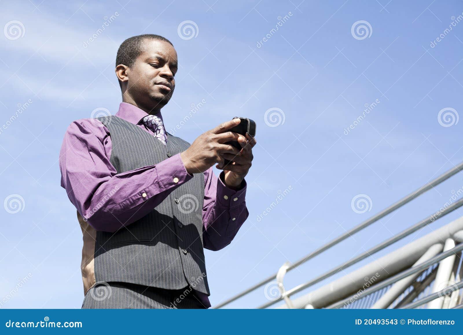 Zwarte bedrijfsmens die met slimme telefoon werkt