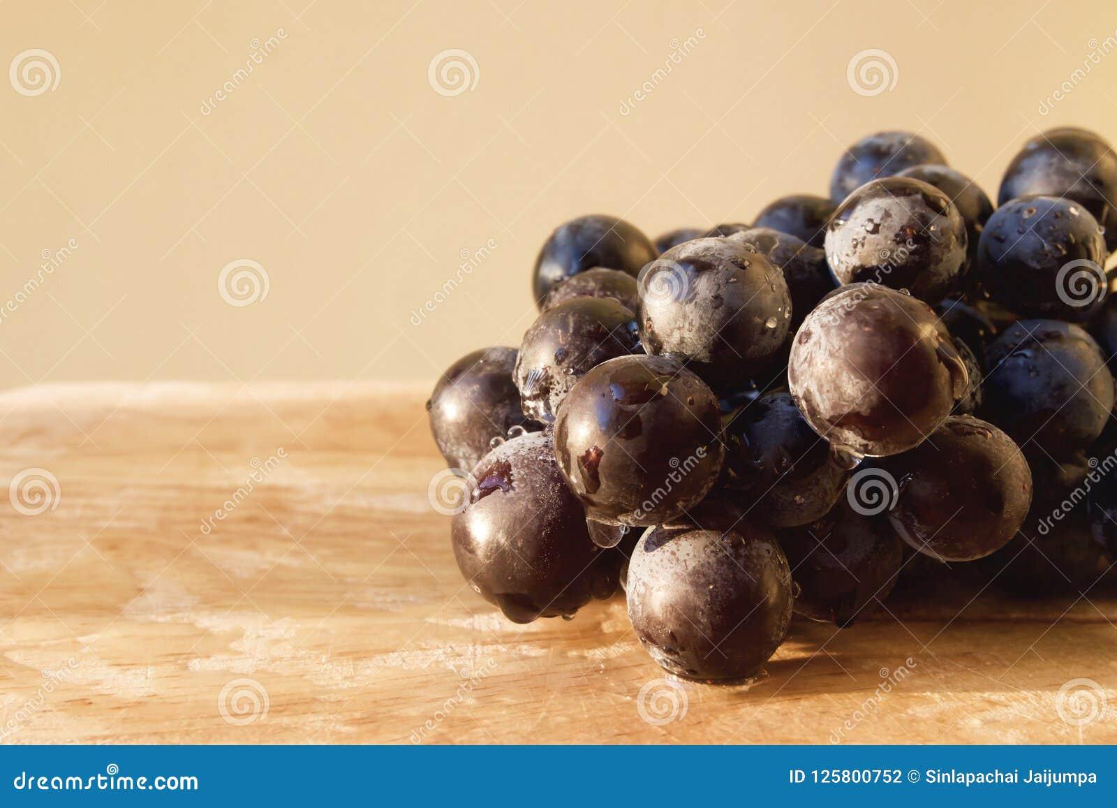 Zwarte druif in houten dienblad met waterdaling en zonlicht De achtergrond van het fruit