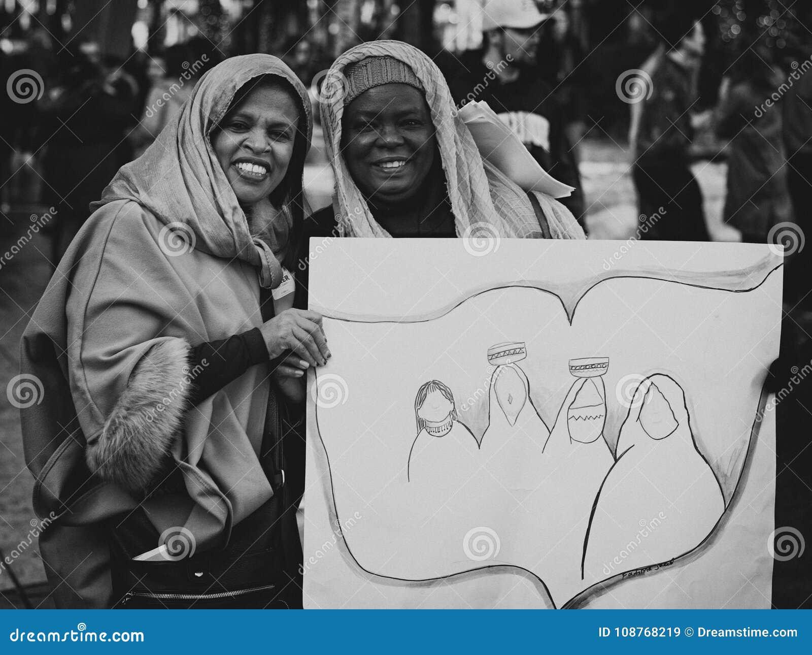 Zwarte en Arabische vrouwen die affiche houden