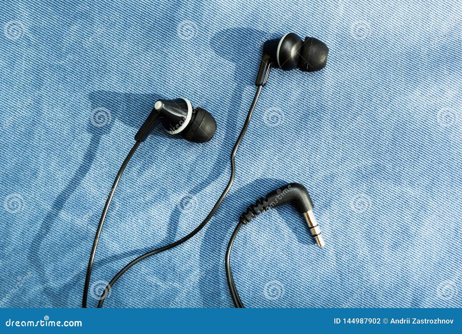 Zwarte hoofdtelefoons met schaduw op jeansachtergrond