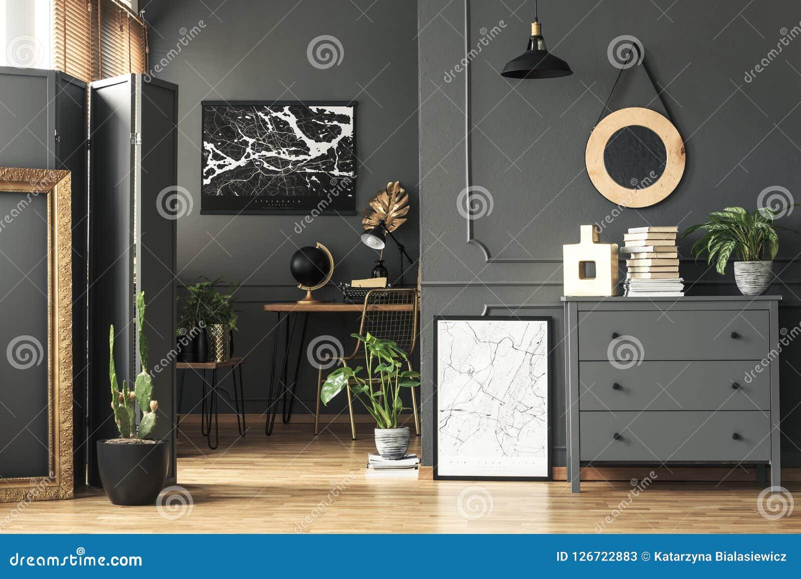 Zwarte kaart op grijze muur in donker woonkamerbinnenland met installaties