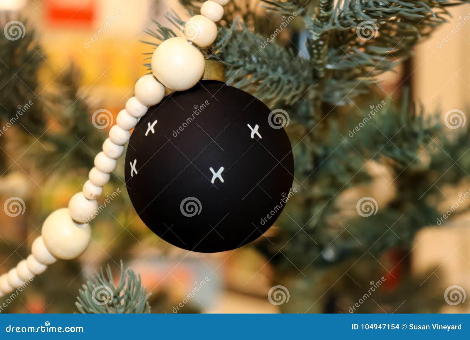 Zwarte Kerstmisbal met witte Xs met andere ornamenten