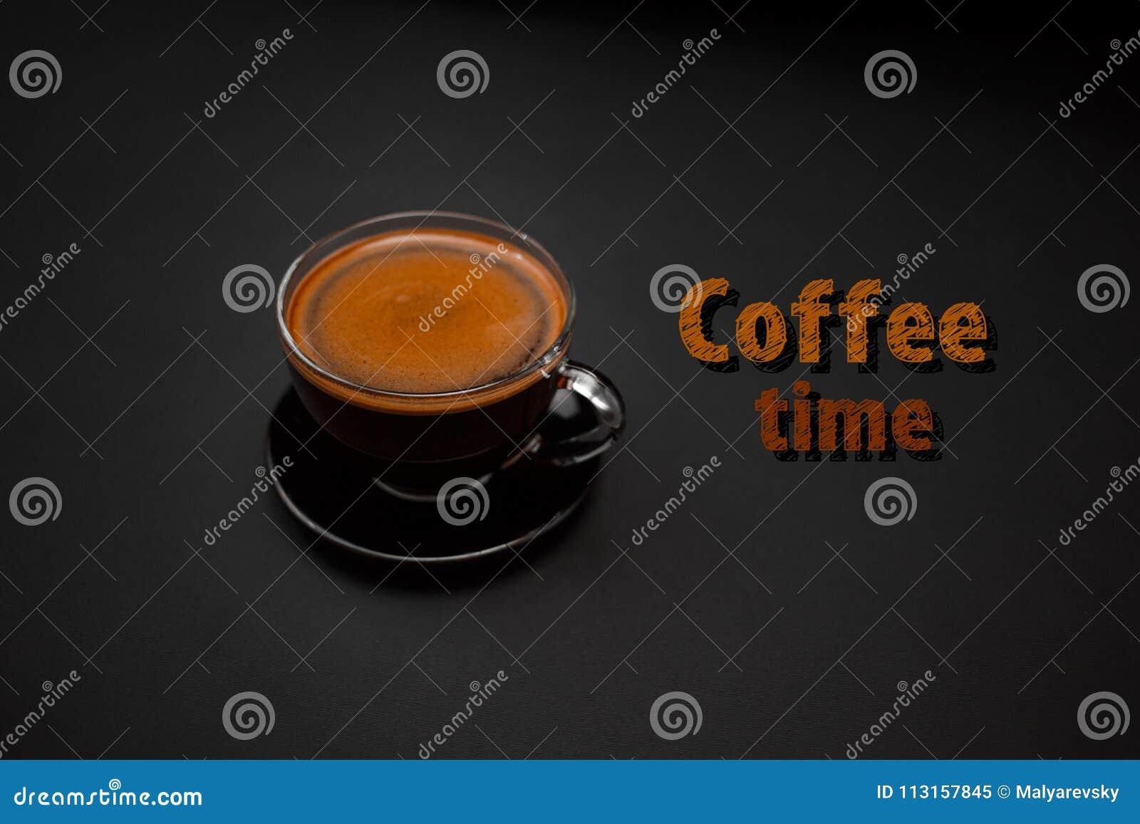 Zwarte, natuurlijke, geurige koffie in de transparante kop op een zwarte achtergrond