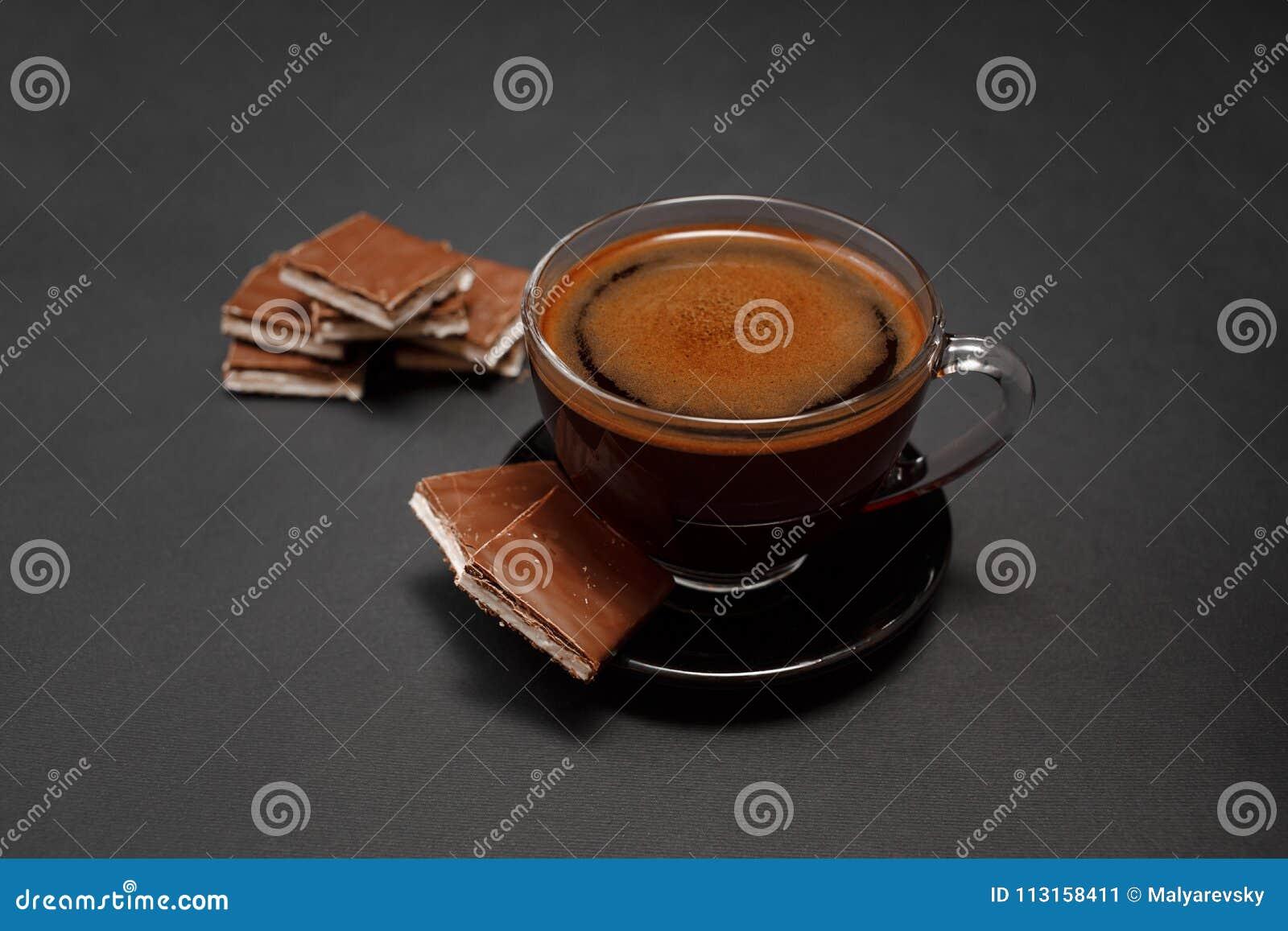 Zwarte, natuurlijke, geurige koffie in de transparante kop op een zwarte achtergrond, met melkchocola