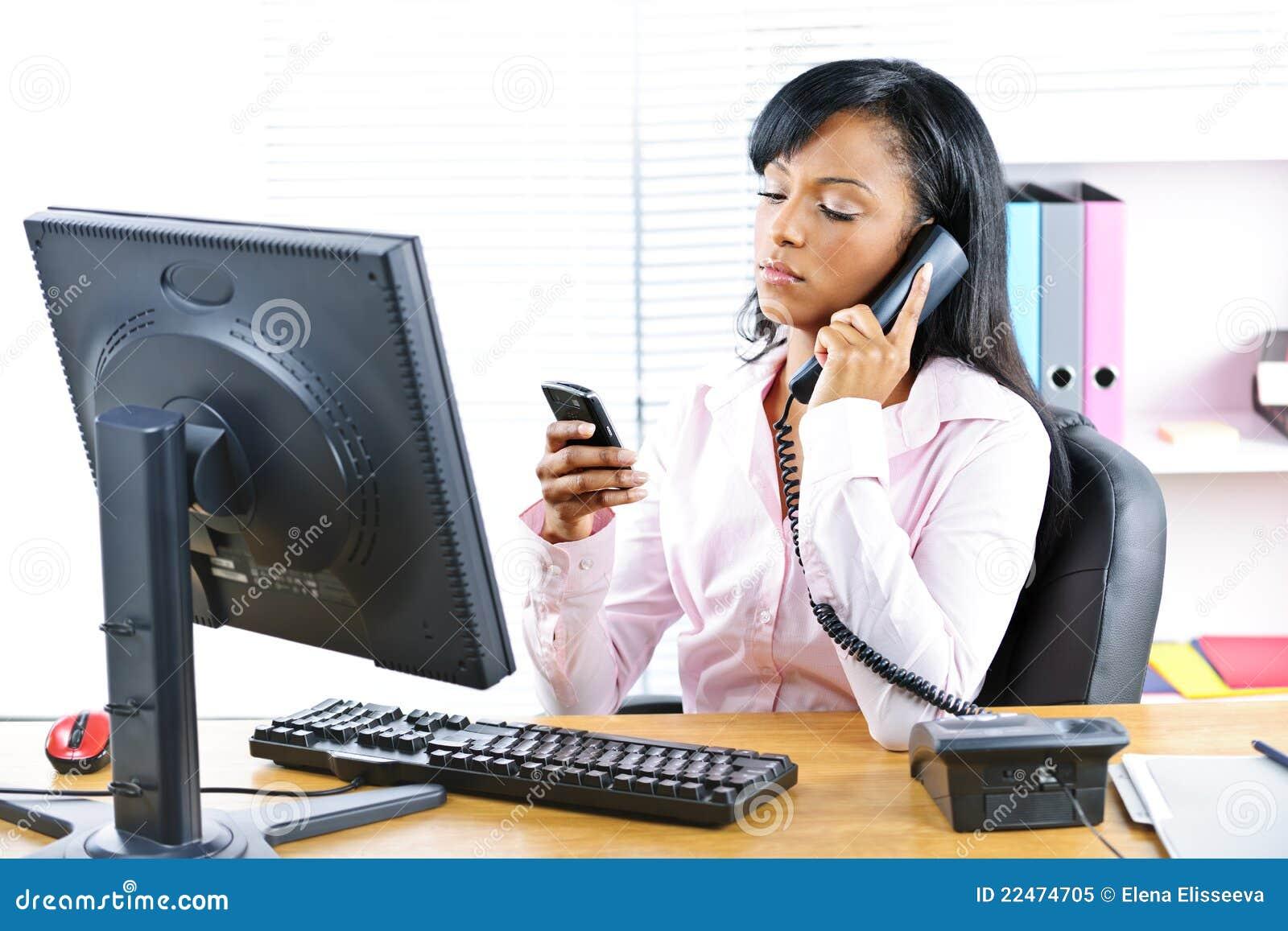 Zwarte onderneemster die twee telefoons met behulp van bij bureau