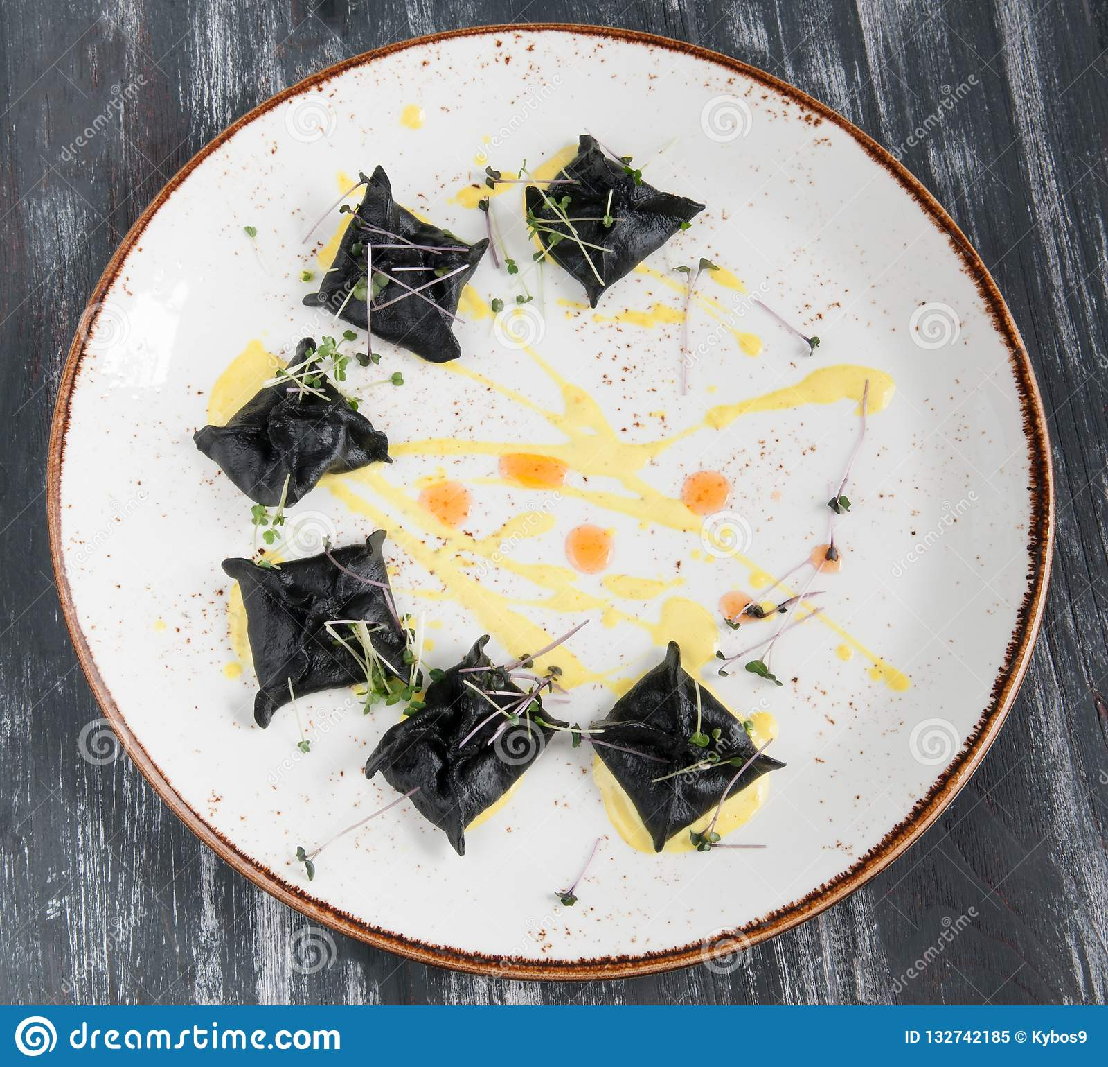 Zwarte ravioli met zeevruchten Op een plaat hoogste mening Op houten zwarte achtergrond