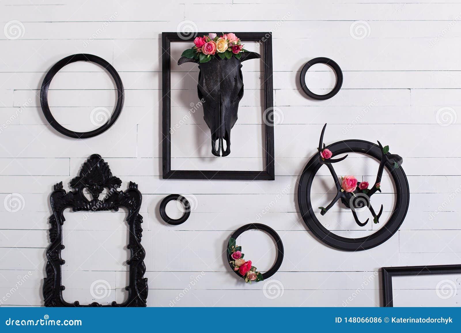 Zwarte schedel van een hert en hoornen op een houten witte muur met lege kaders voor schilderijen Het concept het verfraaien van