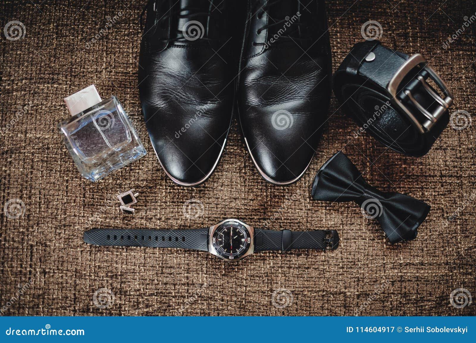 Zwarte schoenen, zwart band, zwart horloge, zwarte vlinder, cufflinks en parfum op een bruine achtergrond met het ontslaan