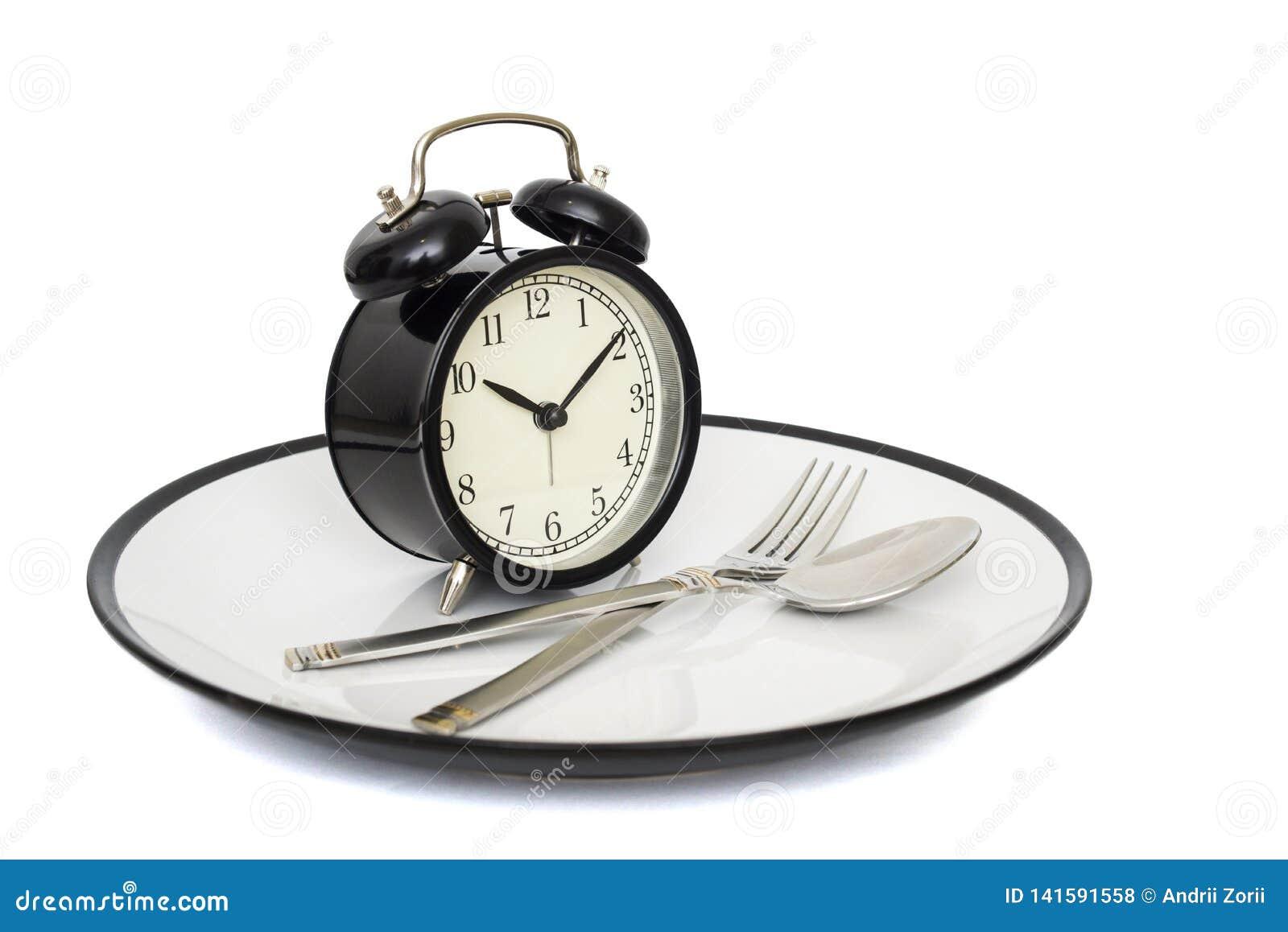 Zwarte wekker met vork en mes op de plaat Geïsoleerd op wit Tijd te eten Gewichtsverlies of dieetconcept