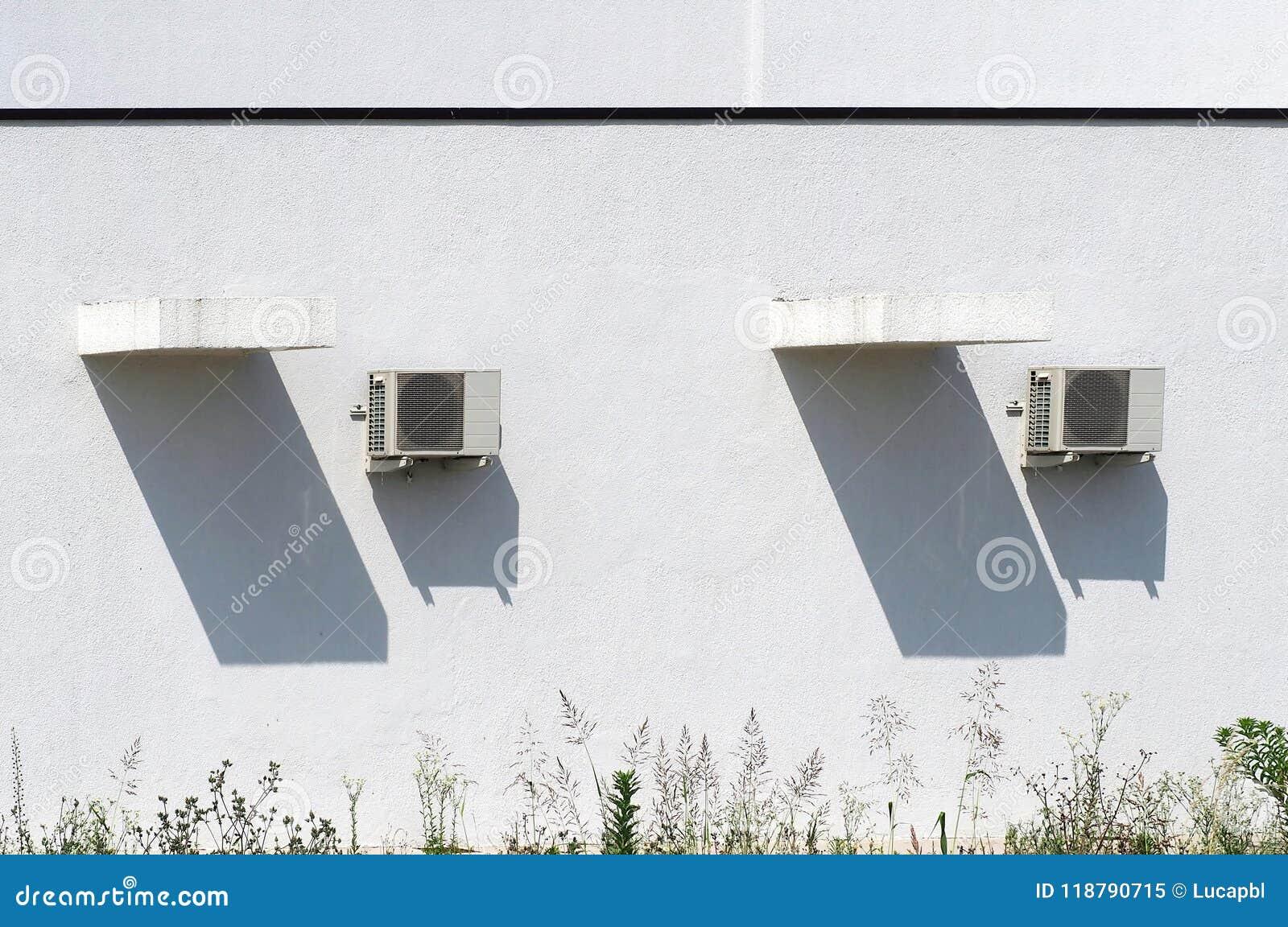 Zwei ÄußerKlimaanlagen und ihre langen Schatten auf einer Ausgangsweißen Wand, unter einem sonnigen Tag des heißen Sommers