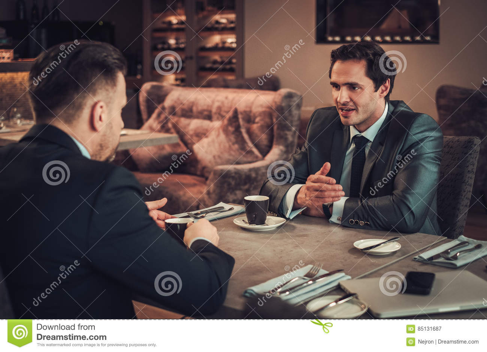 Zwei überzeugte Geschäftsleute essen Business-Lunch am Restaurant zu Mittag