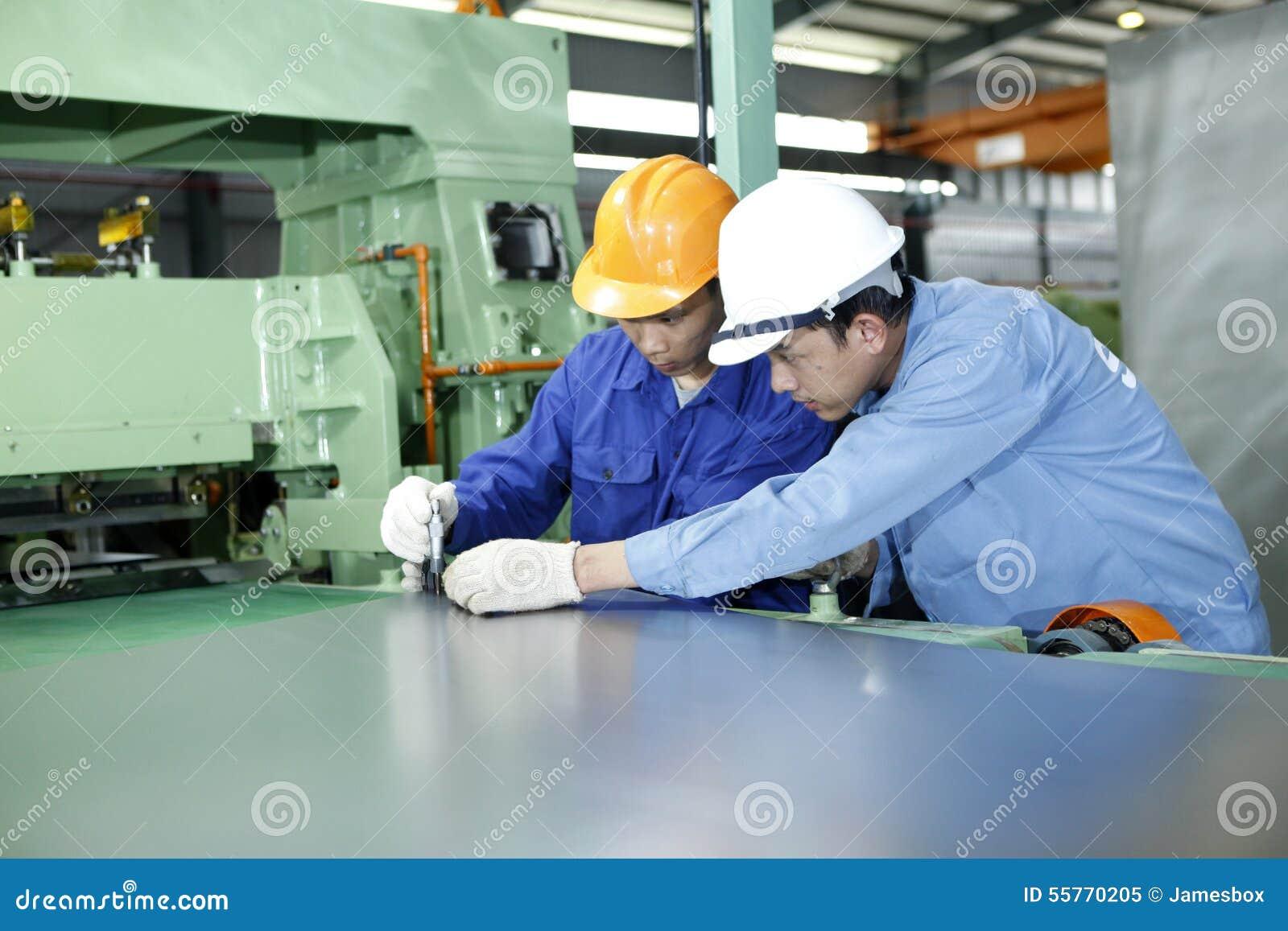 Zwei Arbeitskräfte arbeiten in einer mechanischen Werkstatt