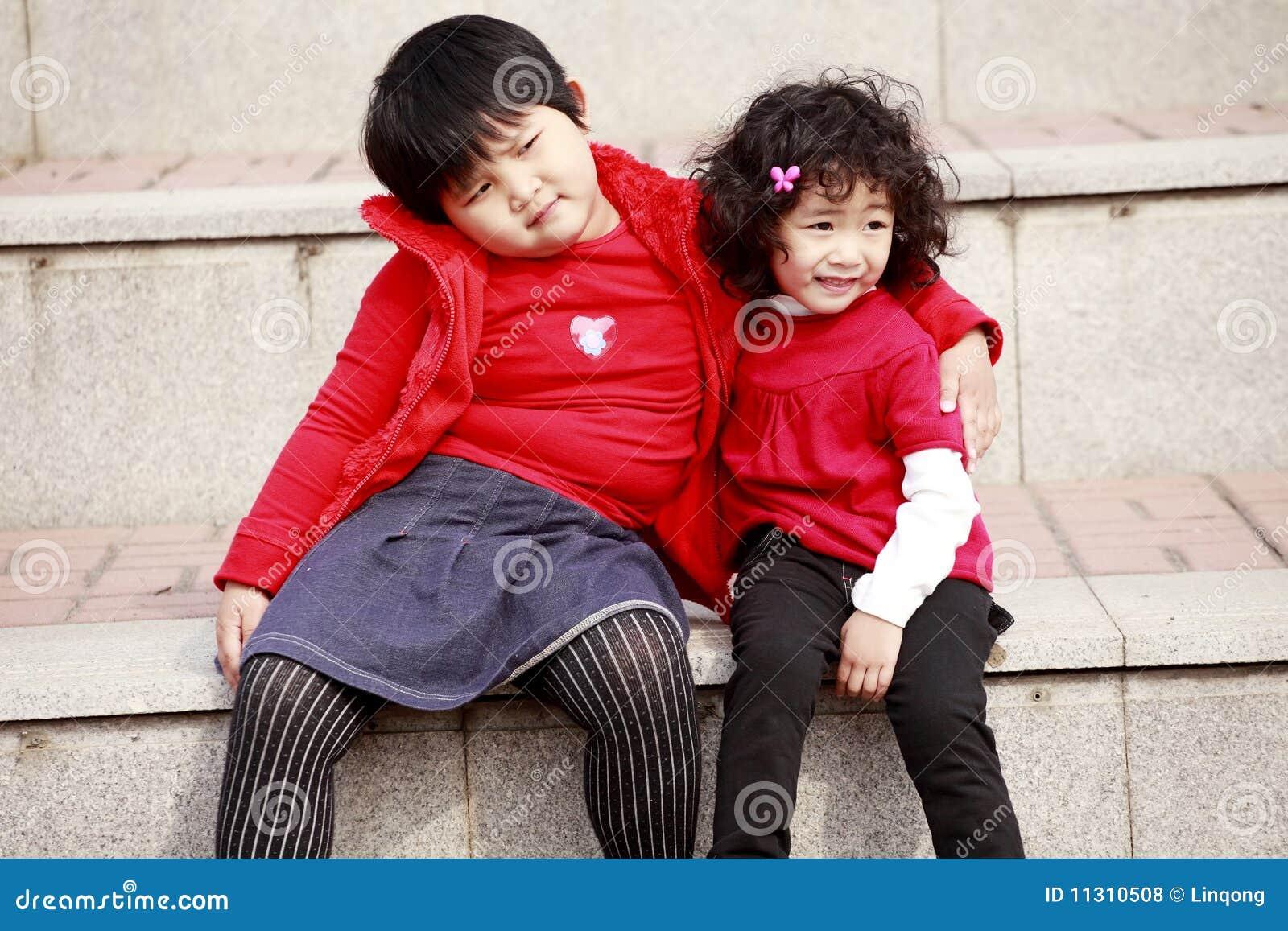 Zwei asiatische kleine Mädchen auf Treppen.