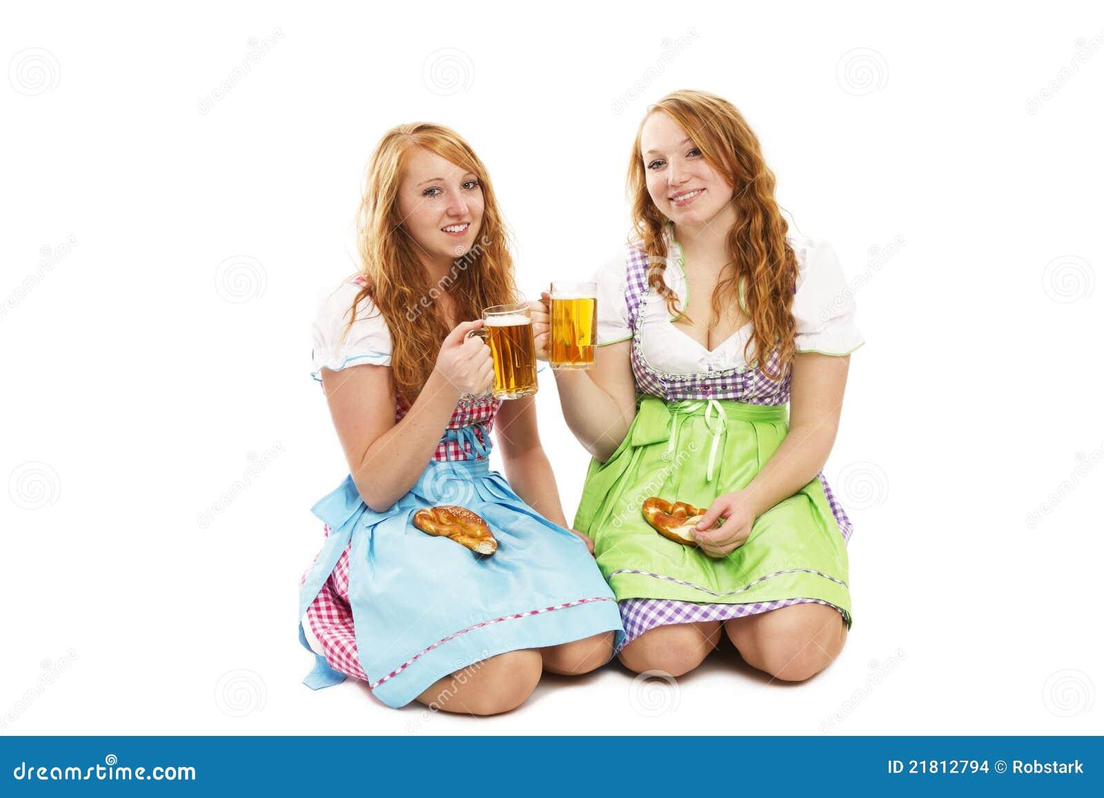 Zwei bayerische mädchen mit brezeln und bier kniend auf fußboden auf