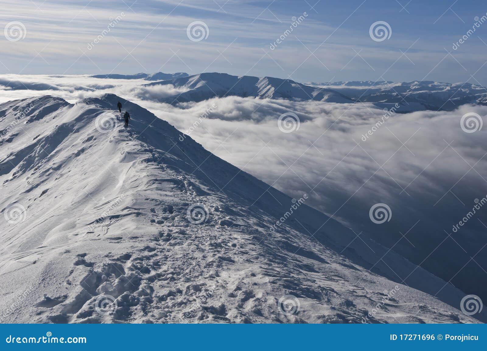Zwei Bergsteiger auf einem Berg übersteigen im Winter