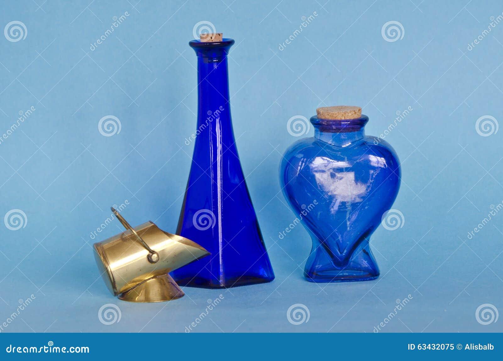Zwei blaue Glasflaschen mit dekorativem Messinggegenstand