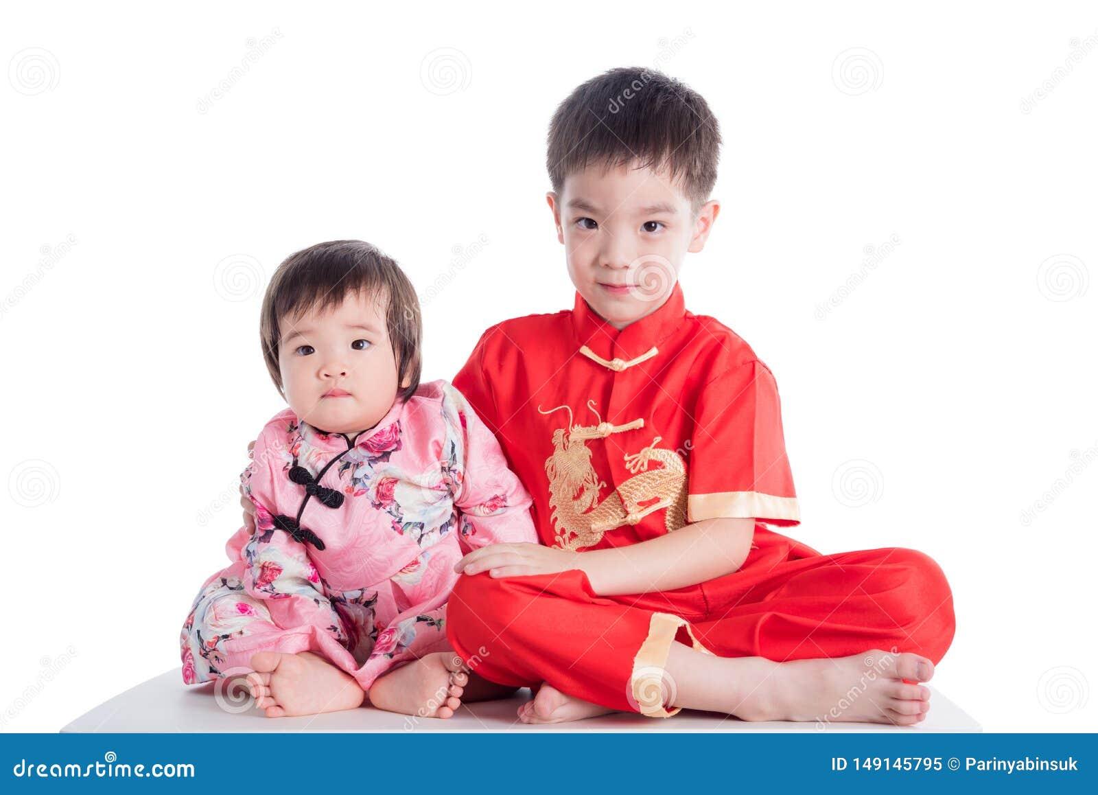 Zwei chinesische Kinder, die das traditionelle Kostüm sitzt auf dem Boden über Weiß tragen