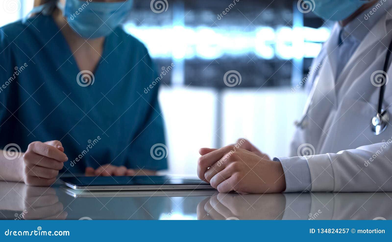 Zwei Doktoren, die Testergebnisse auf Tablette überprüfen und geduldige Diagnose besprechen