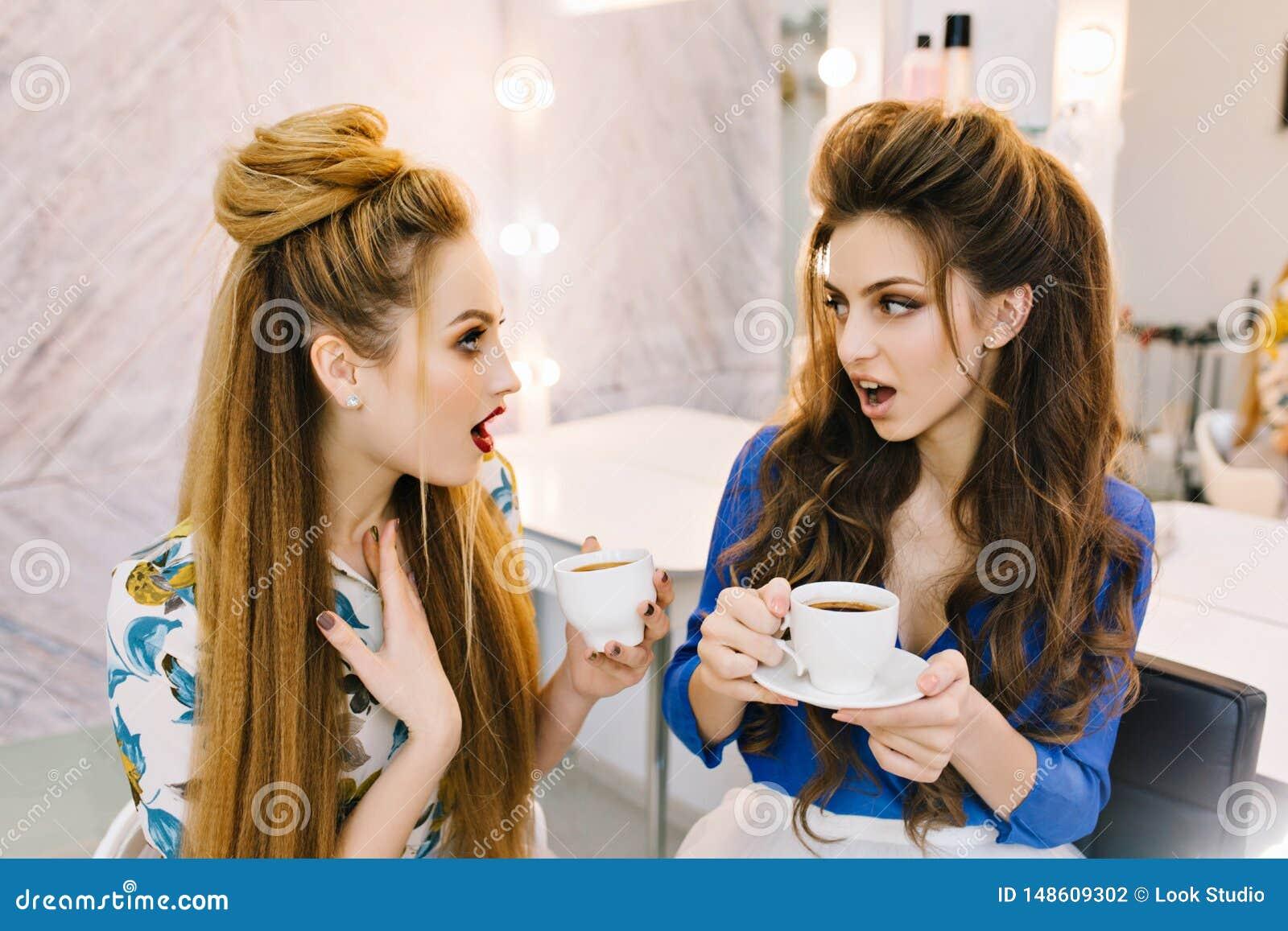 Zwei erstaunt ?berraschten die attraktiven Frauen, die im Sch?nheitssalon sprechen Trinkender Kaffee, bereitend zur Partei vor un