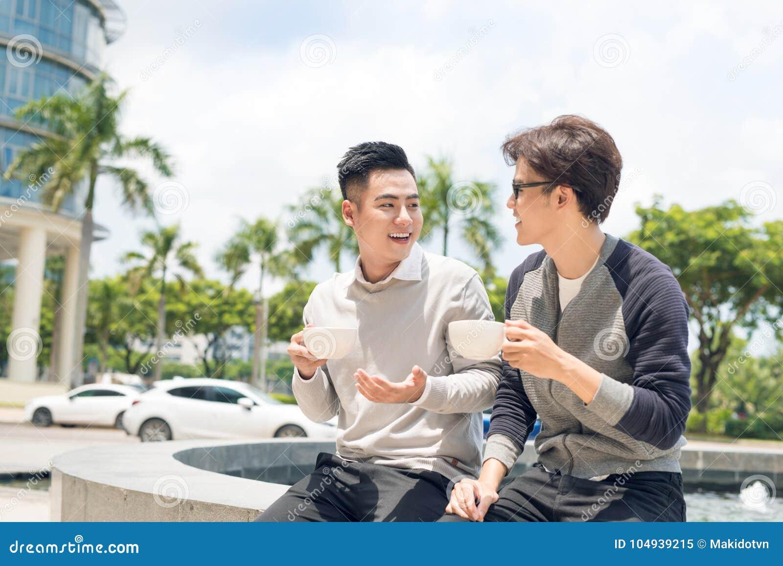 Zwei erwachsener Mannesfreunde sitzen die Unterhaltung über Kaffee außerhalb des Cafés
