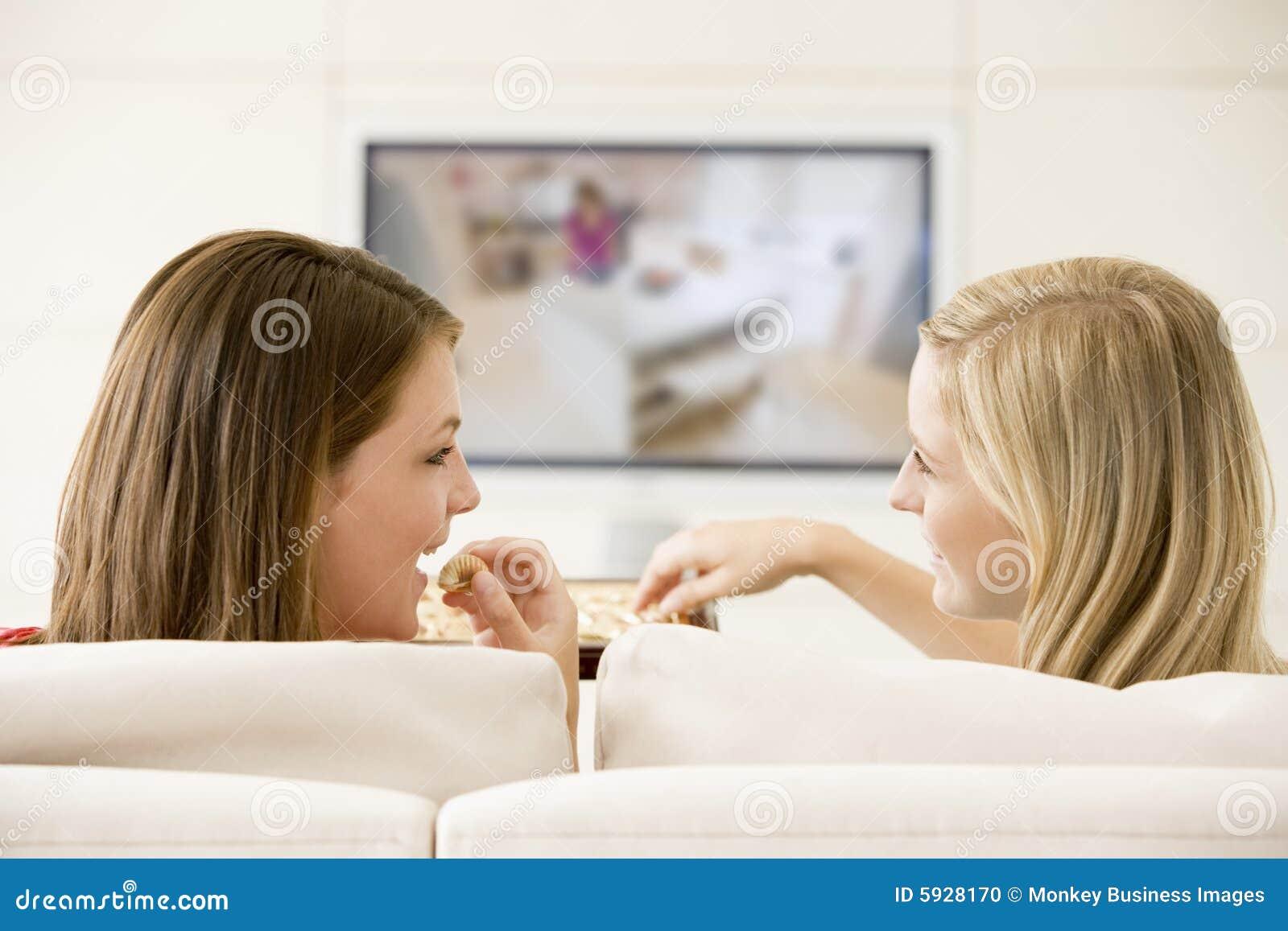 Zwei Frauen in überwachendem Fernsehen des Wohnzimmers